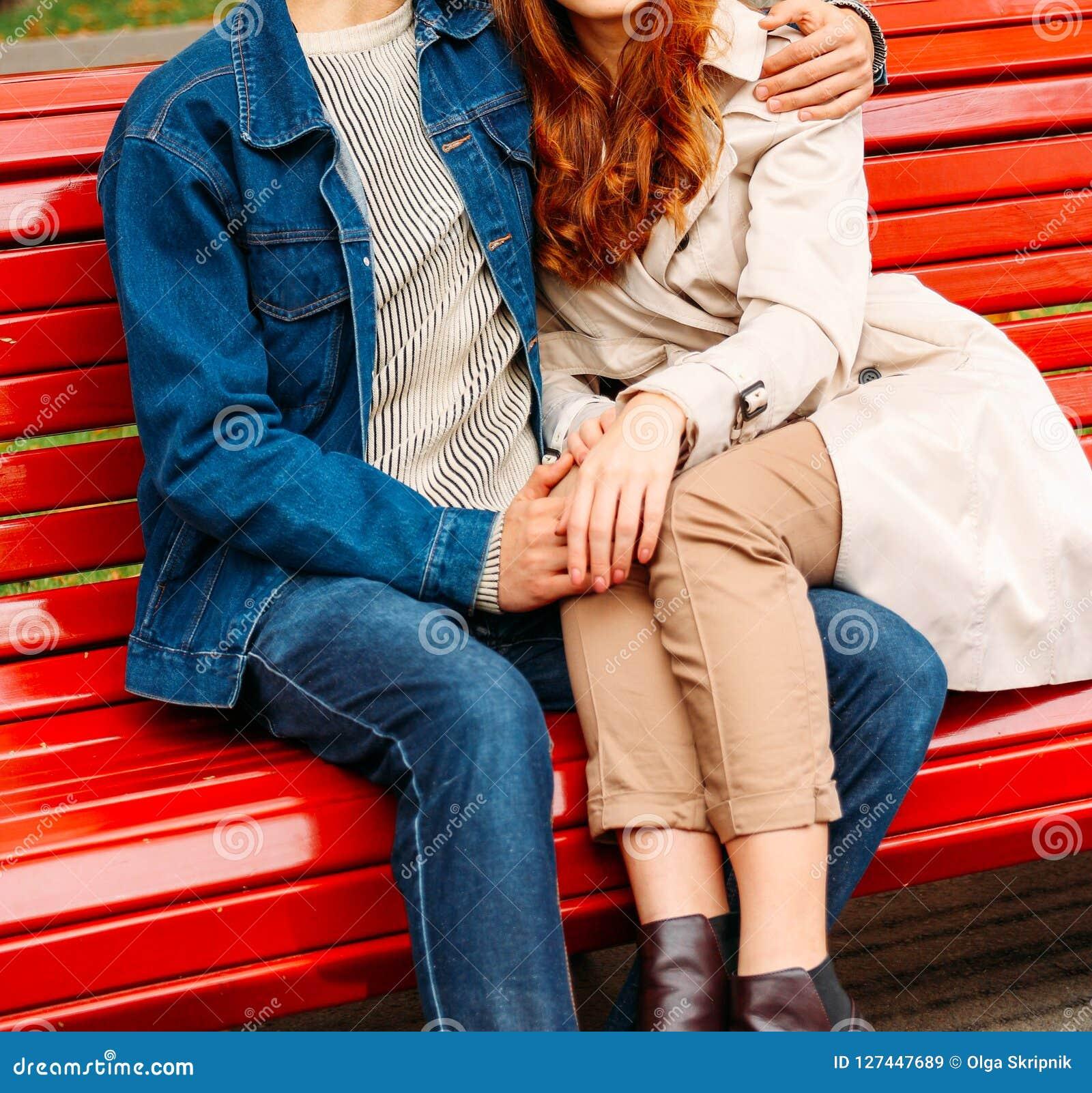 Paarzitting op een bank, benen van een meisje op een kerel, een man die een vrouw koesteren een kerel in jeans en een denimjasje,