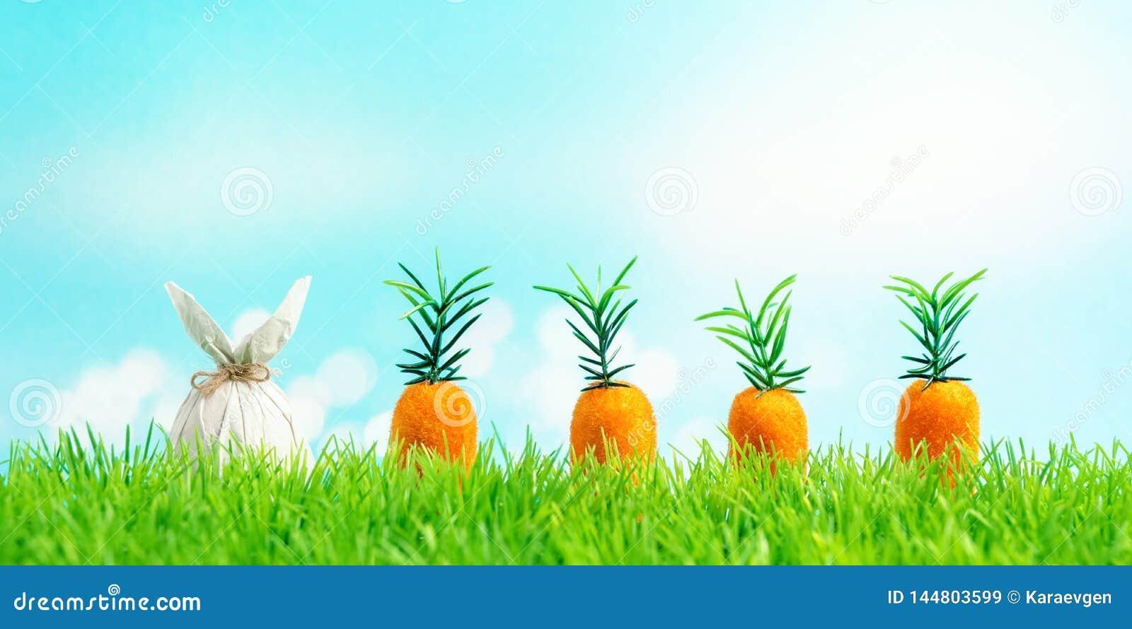 Paasei in een document in de vorm van een konijntje met wortel op groen gras wordt verpakt dat Het concept van de de lentevakanti