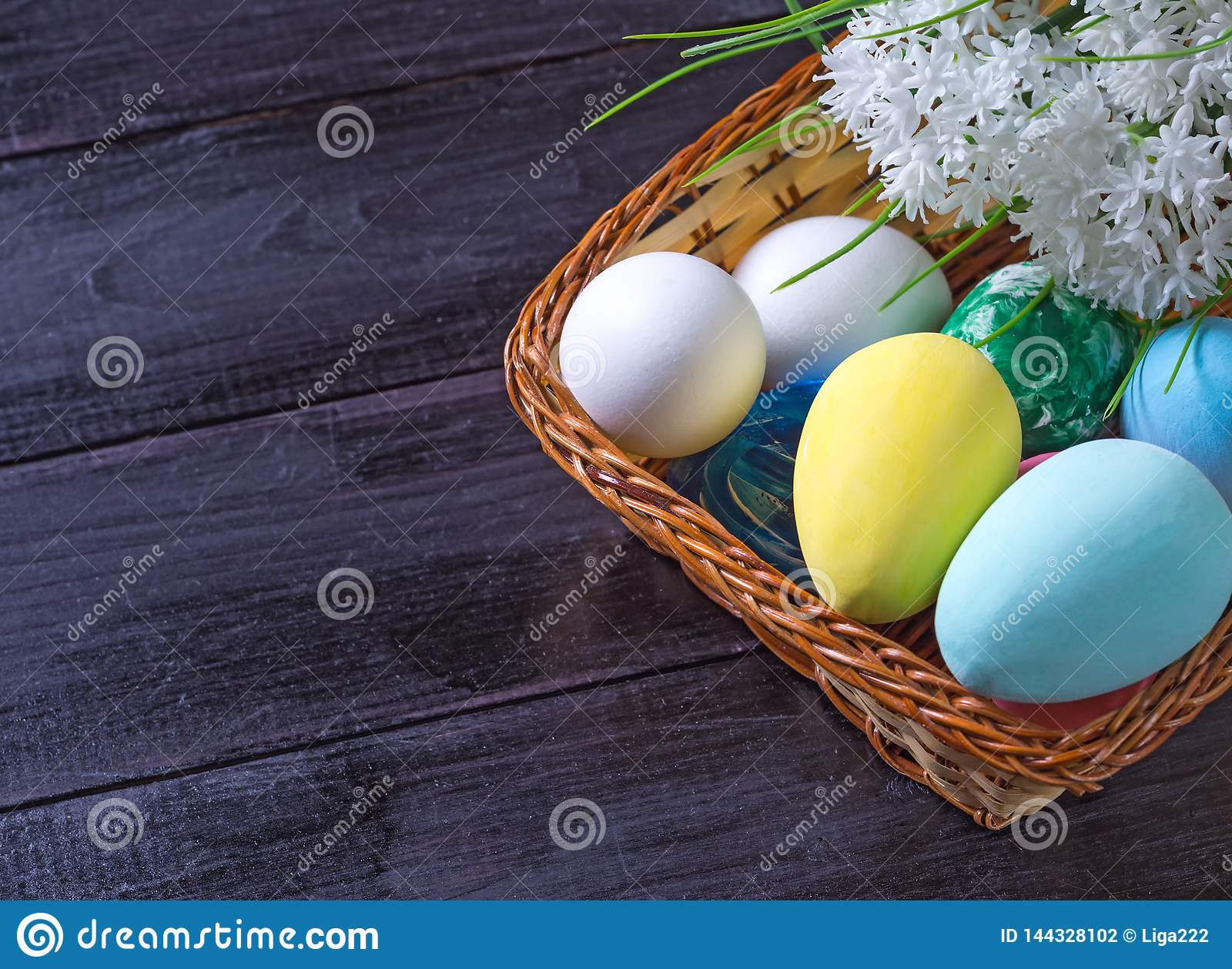 Paaseieren in een mand en witte bloemen op een donkere houten achtergrond