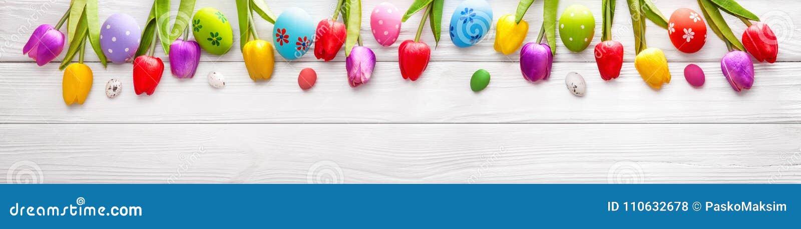Paaseieren met bloemen op houten achtergrond