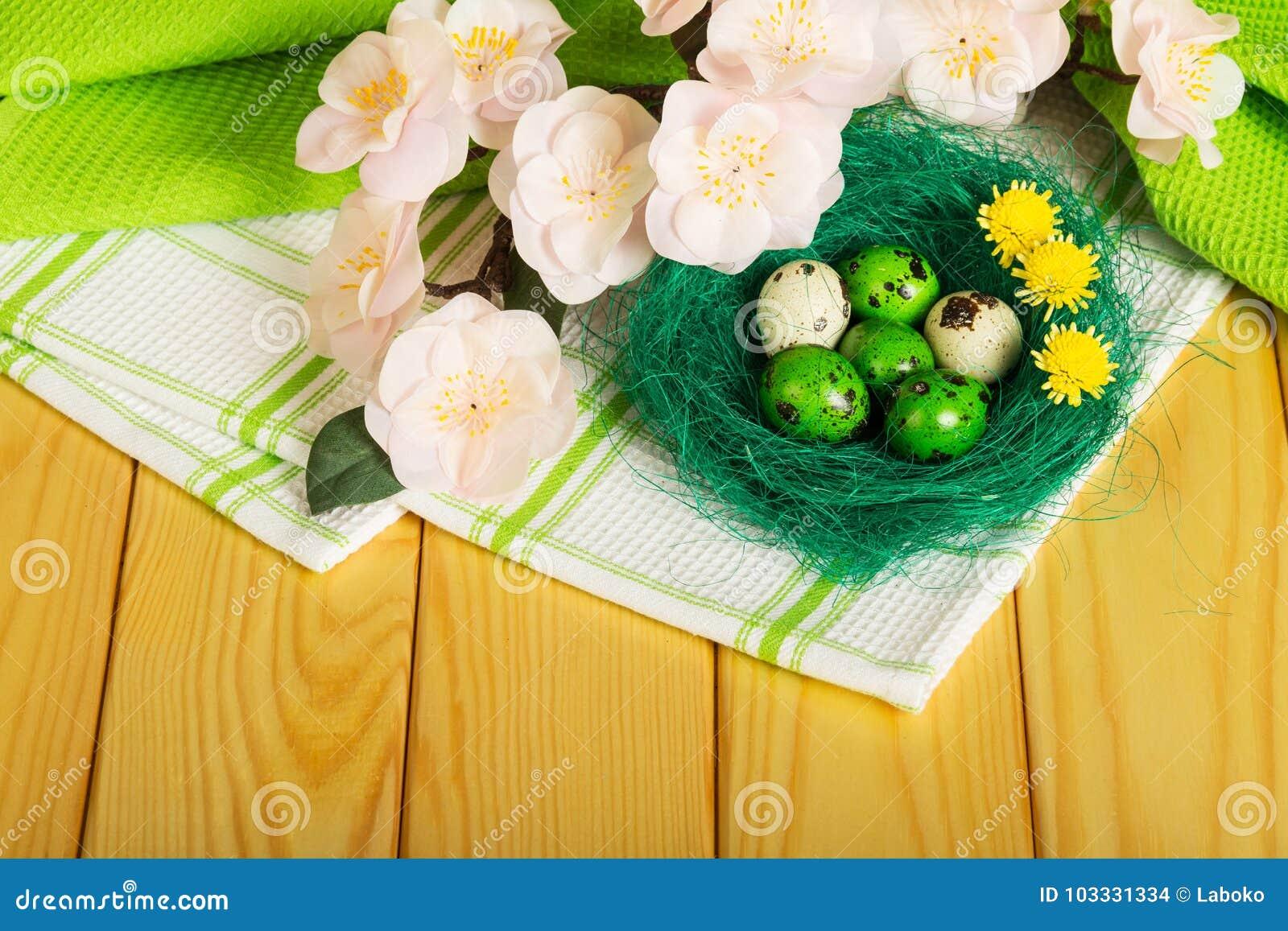 Paaseieren in nest, bloemen op handdoek en lichte boom