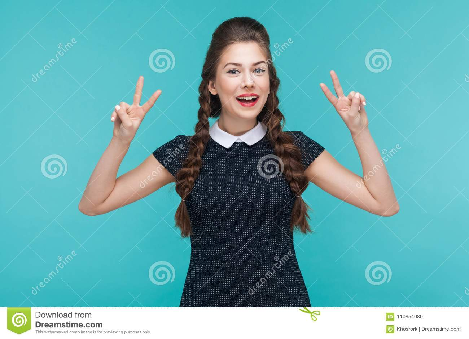 Pace, sguardo ottimista! Giovane donna di felicità che mostra il segno di v