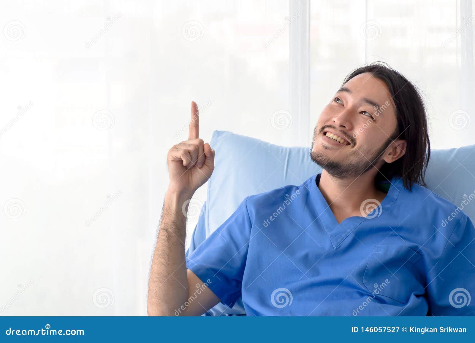 Paciente asiático de sorriso que senta-se na cama de hospital com o dedo que aponta acima