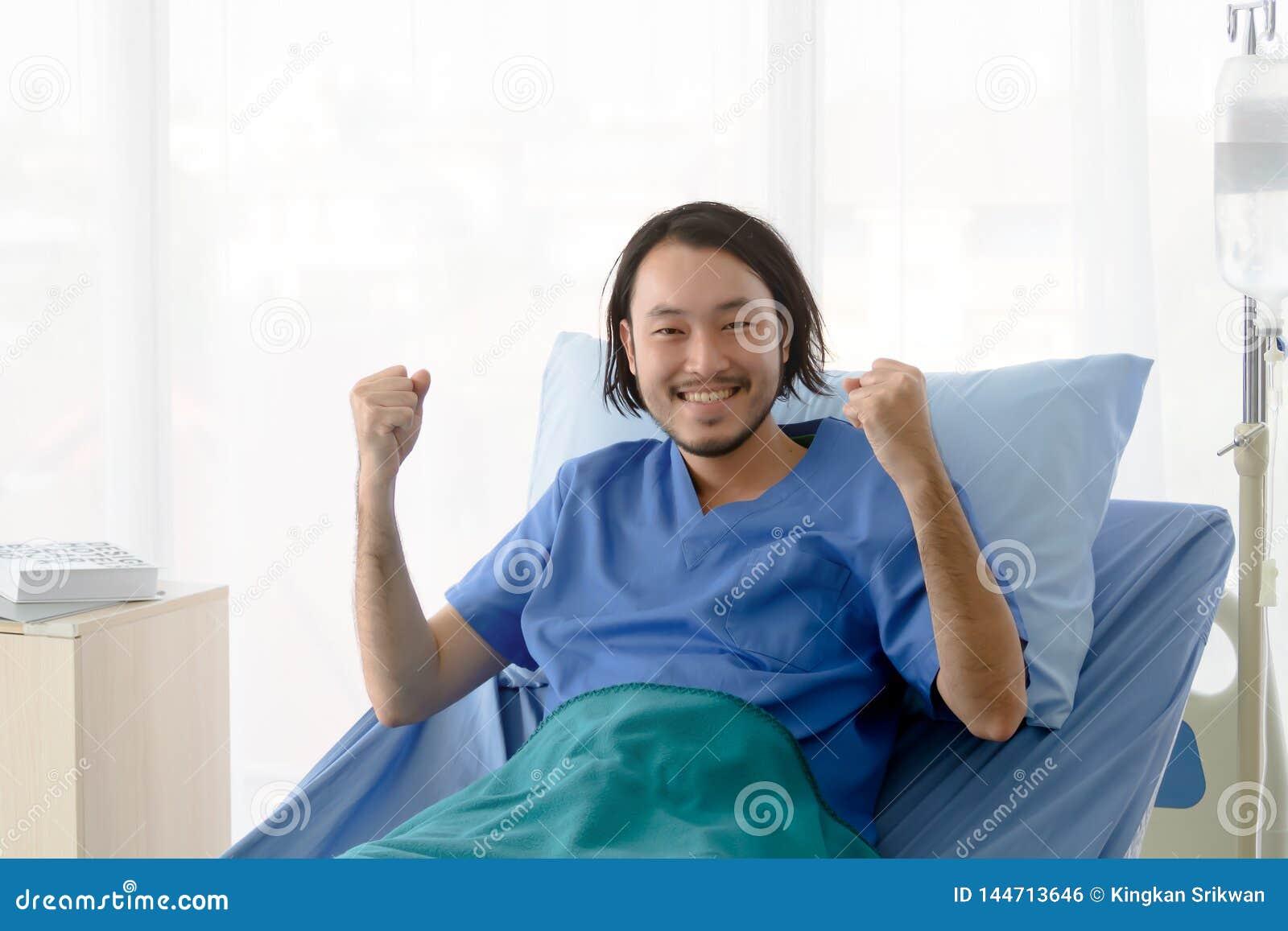 Paciente asi?tico que senta-se na cama de hospital com levantamento dos bra?os