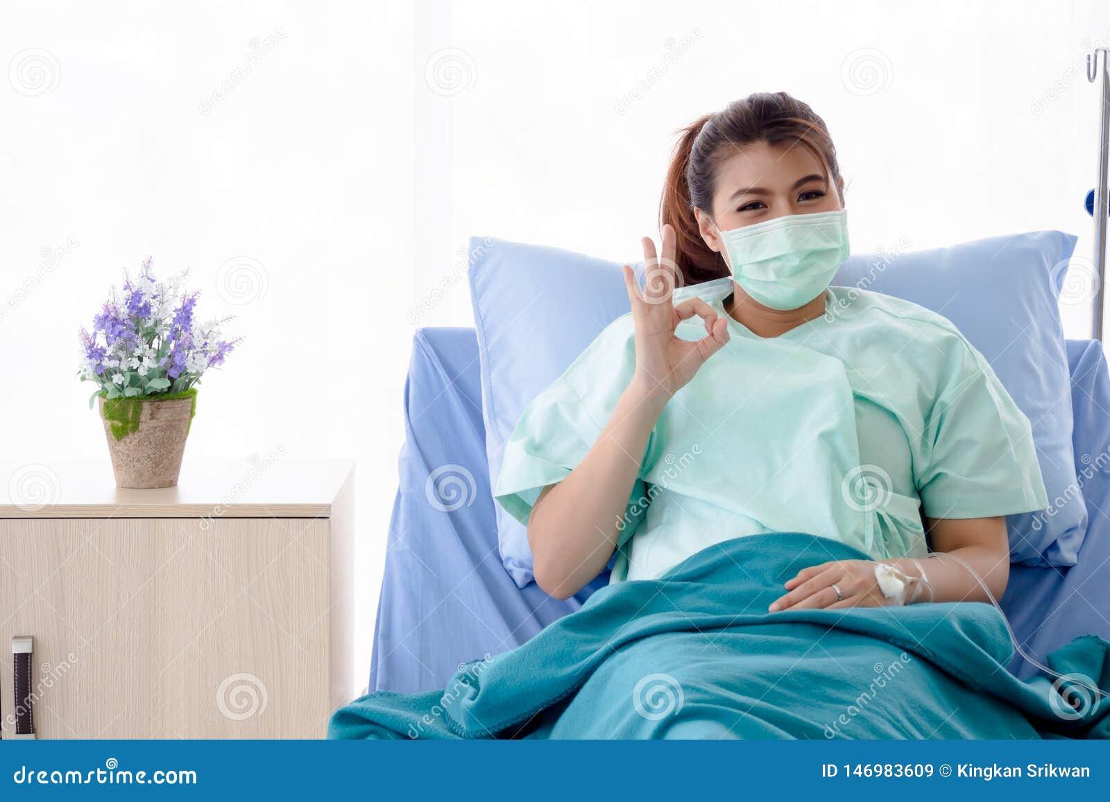 Paciente asiático que senta-se na cama de hospital, o sinal APROVADO do gesto de mão da jovem senhora