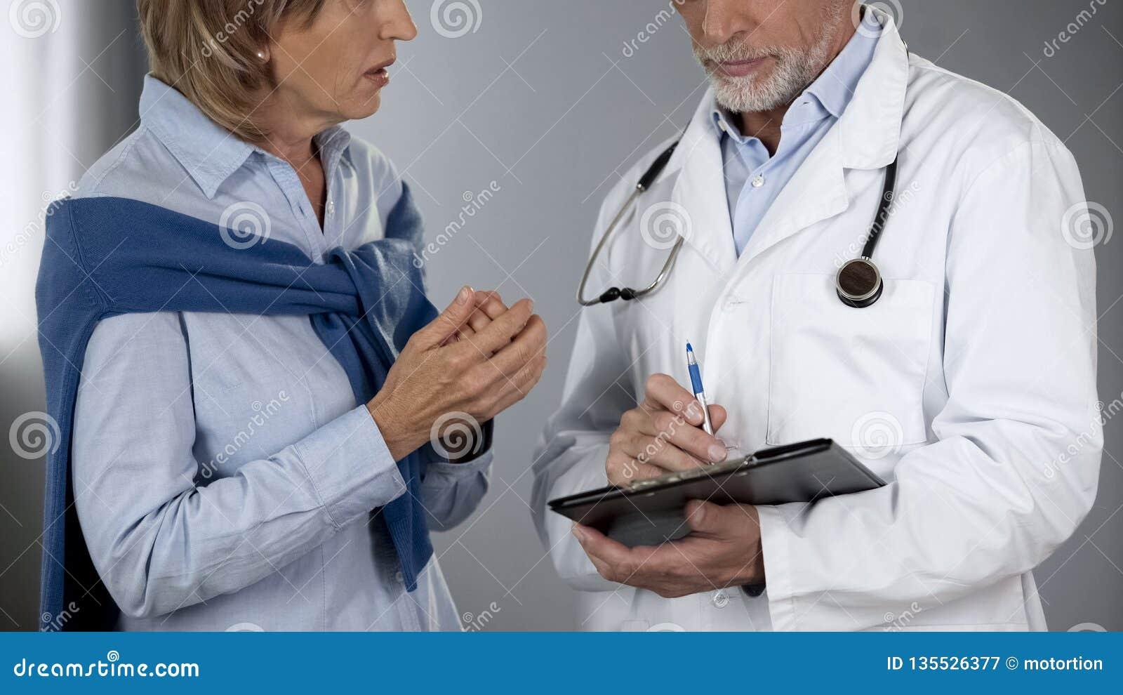 Paciente fêmea que fala para medicar sobre os resultados da análise, chocados pelo diagnóstico