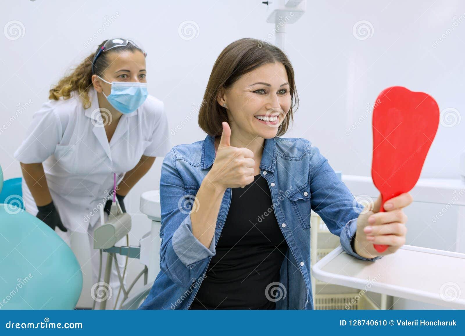 Paciente feliz da mulher que olha no espelho nos dentes, sentando-se na cadeira dental