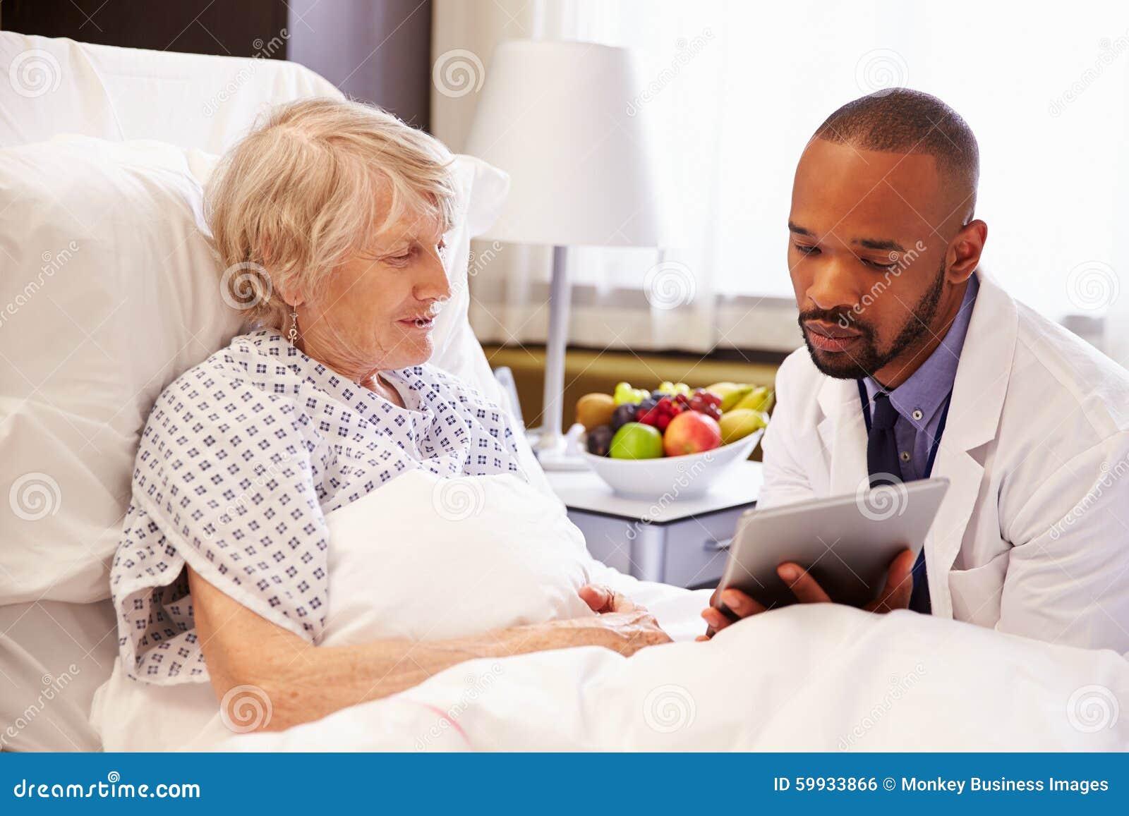 Paciente femenino del doctor Talking To Senior en cama de hospital