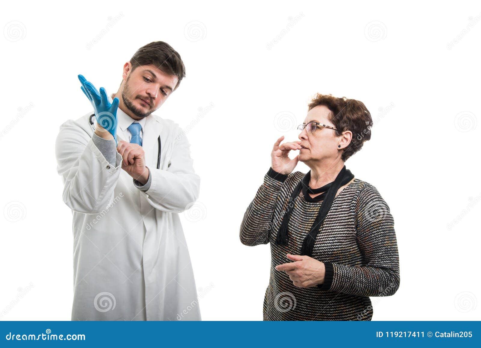 Paciente femenino preocupante que mira al doctor de sexo masculino que pone el guante azul