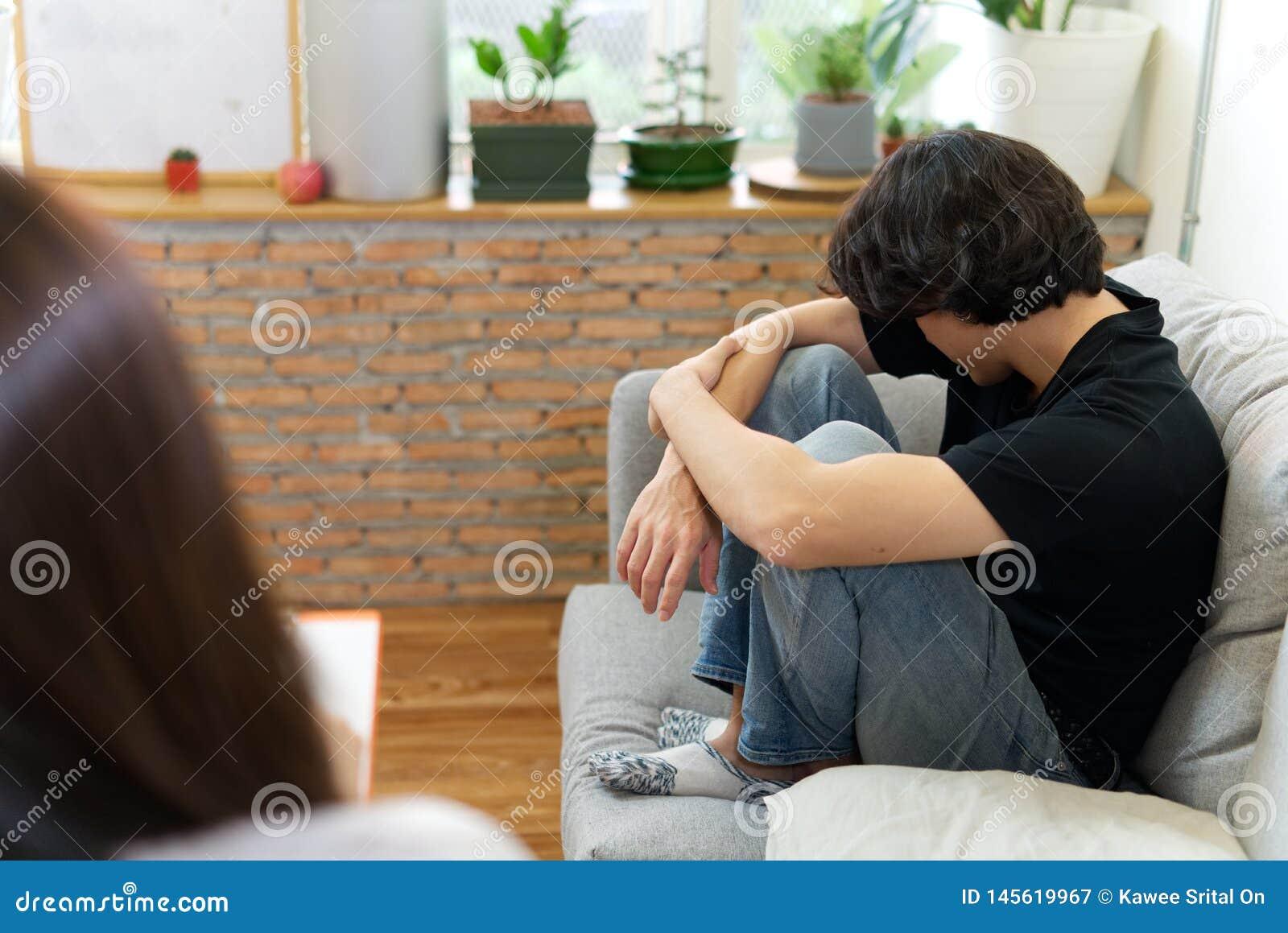 Paciente masculino joven que se sienta en el sof? con la cara triste que consulta con el psic?logo
