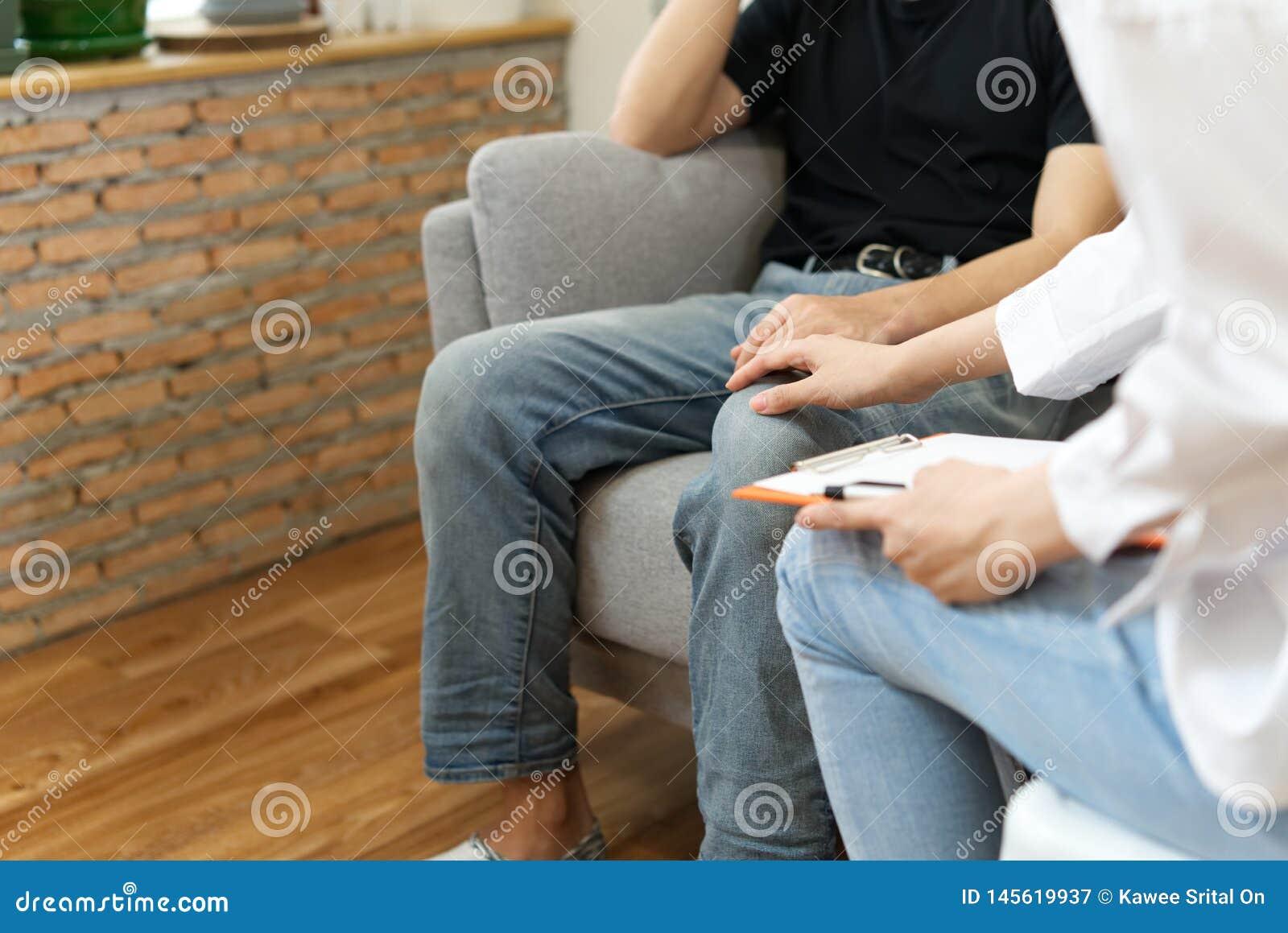 Paciente masculino novo que senta-se no sofá com a cara triste que consulta com o psicólogo