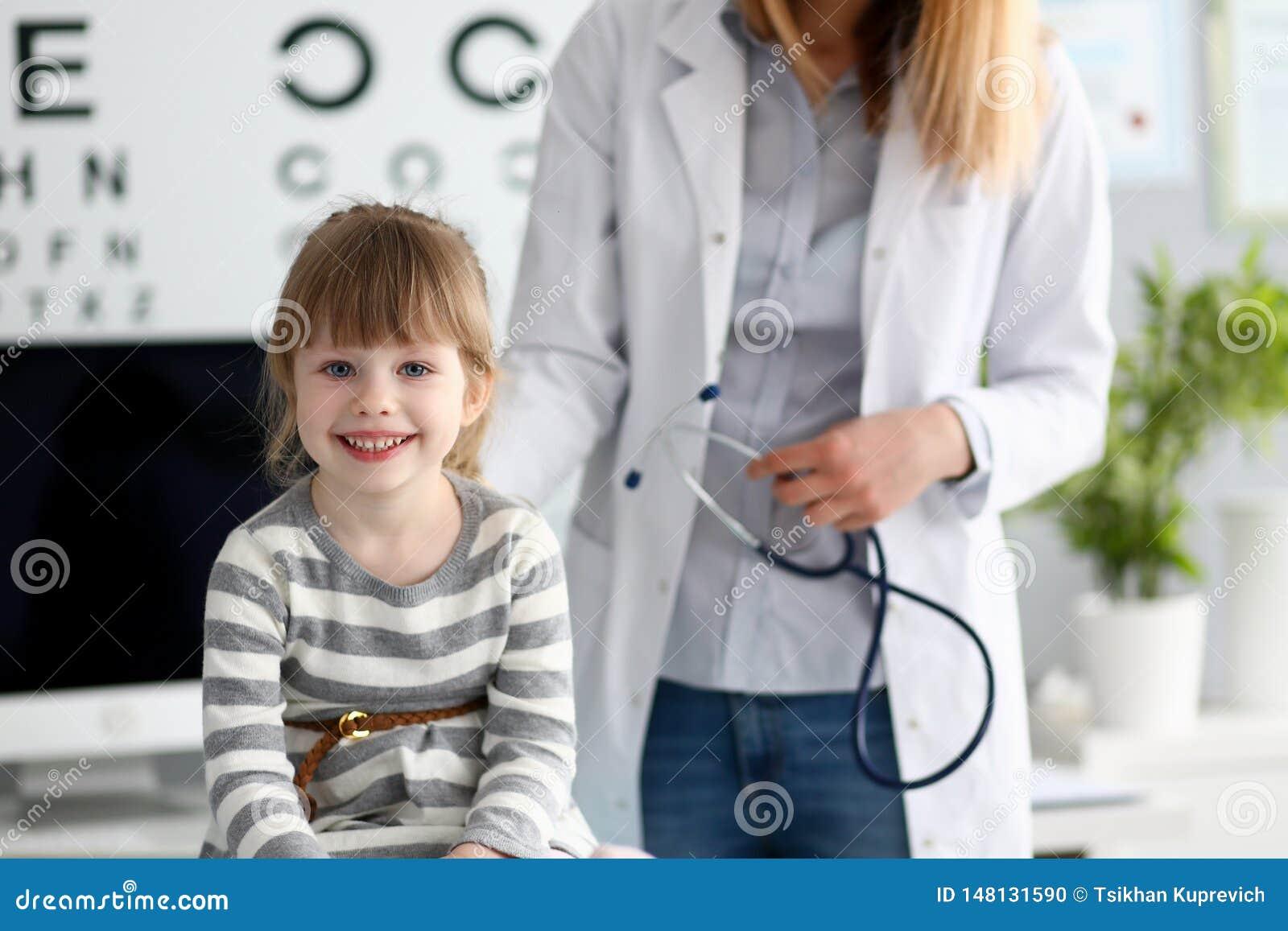 Paciente pequeno bonito de sorriso que interage com o doutor fêmea