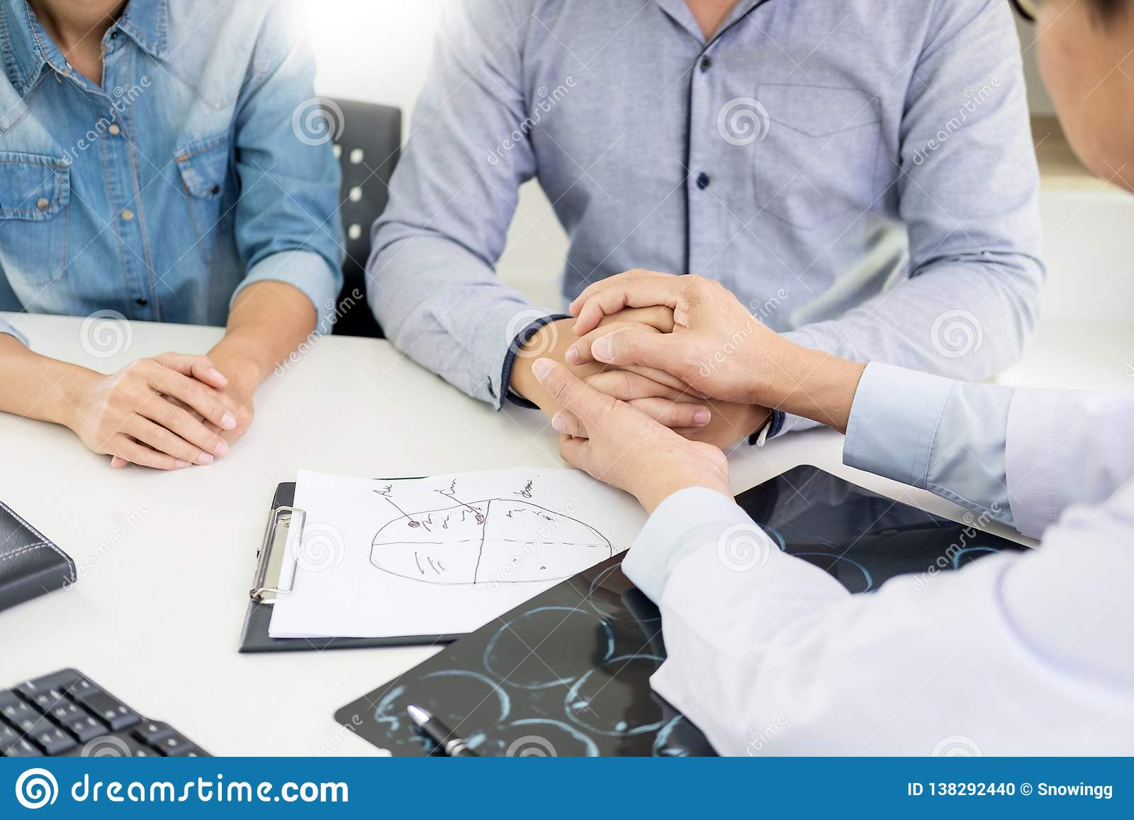 Paciente que é mão guardando desesperada tranquilizada por apoio encorajador do doutor e que consola com simpatia Na sala de hosp