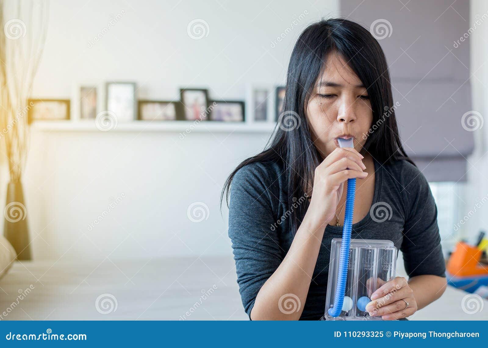 Pacientes asiáticos de la mujer que usan incentivespirometer o tres bolas para la respiración paciente profunda