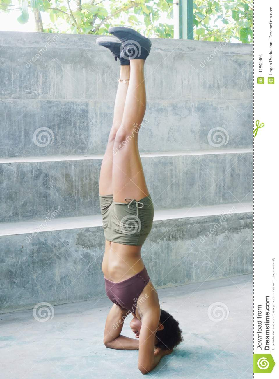 Pacific islander athlete girl with afro performing exercising routines headstand