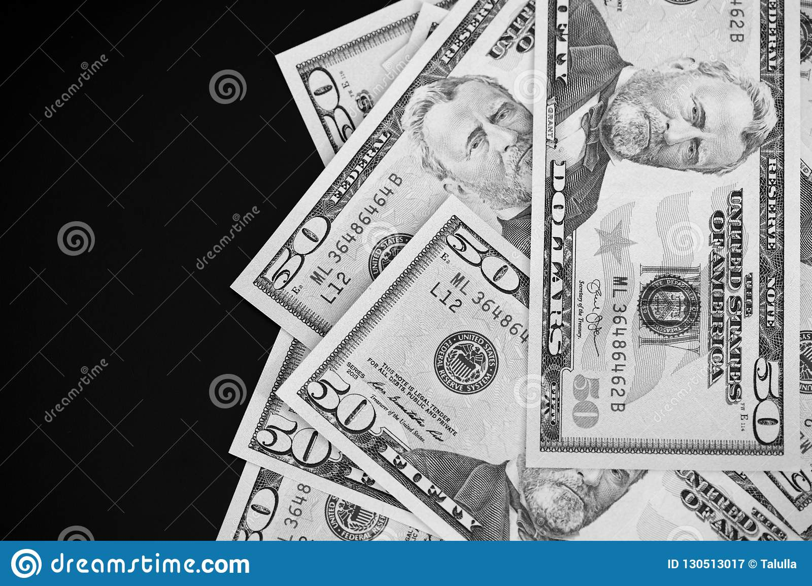 0bcab67dbc3b A pack of fifty dollar bills on a dark background close up. Black and white