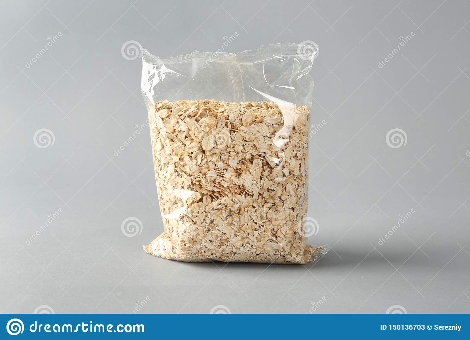 Package with raw oatmeal on light background