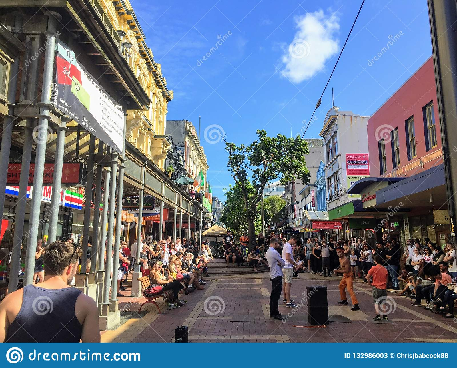 A packed crowd of tourists and locals enjoy a local street performer on Cuba street in downtown Wellington.