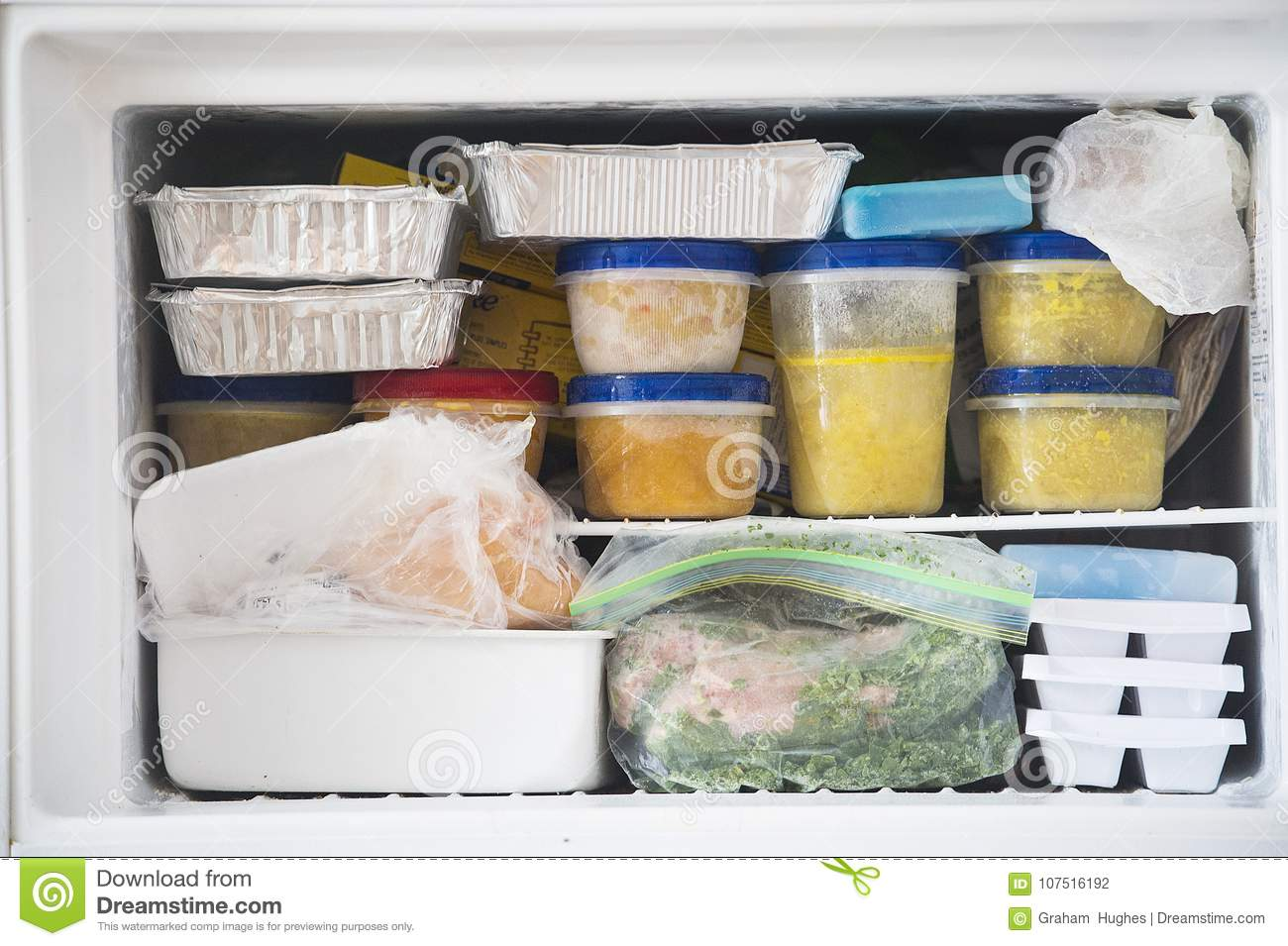A packed freezer with soup and chicken