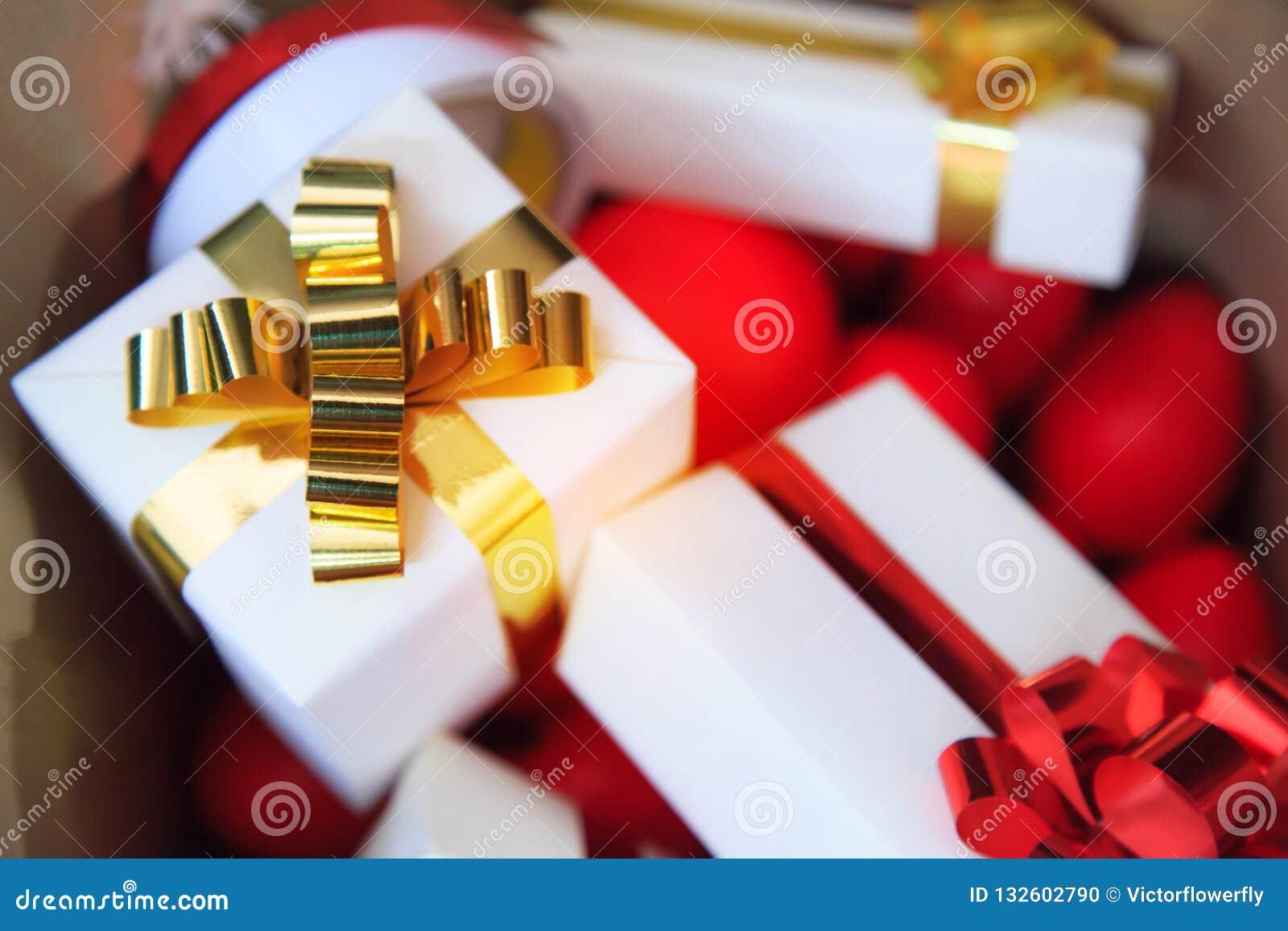 Pacotes e corações vermelhos nas caixas atuais do saco marrom com ouro e fitas vermelhas como caixas de presente de época natalíc
