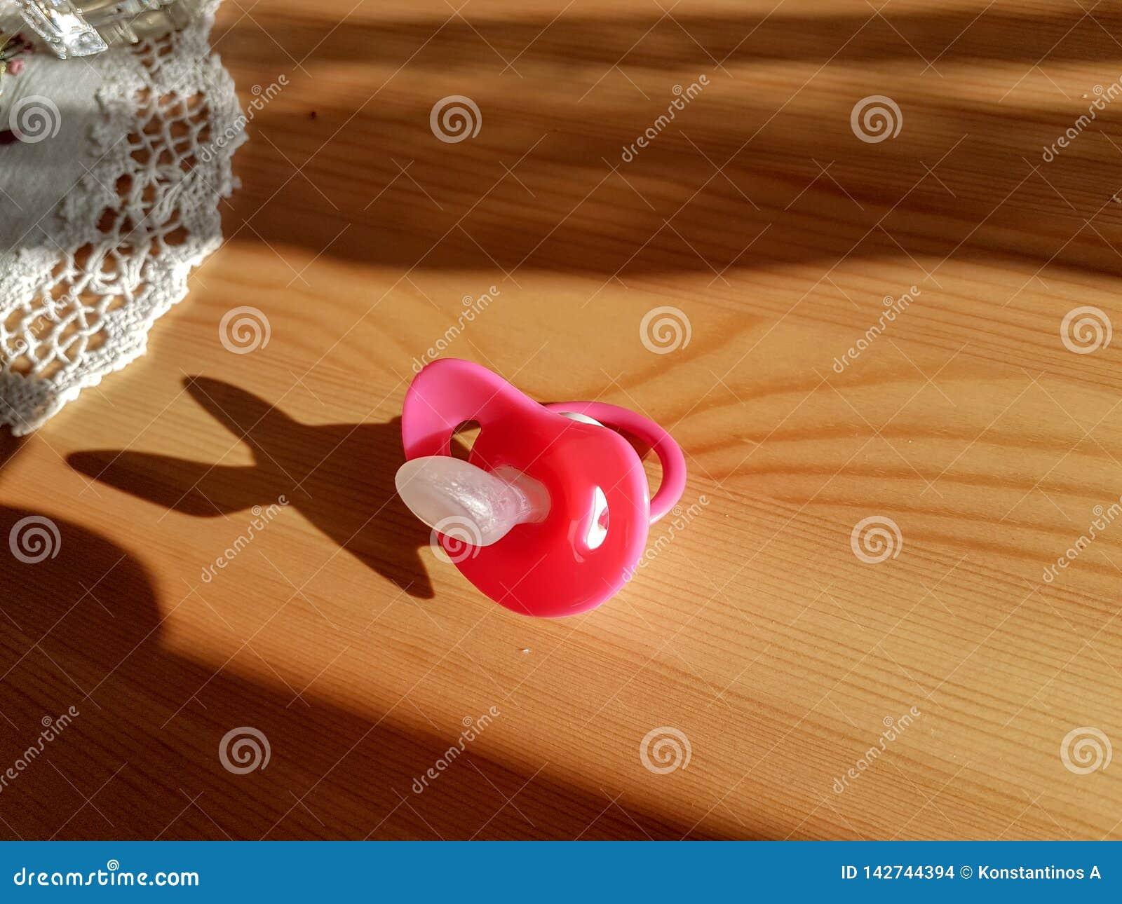 Pacyfikator czerwień na drewnianym stole