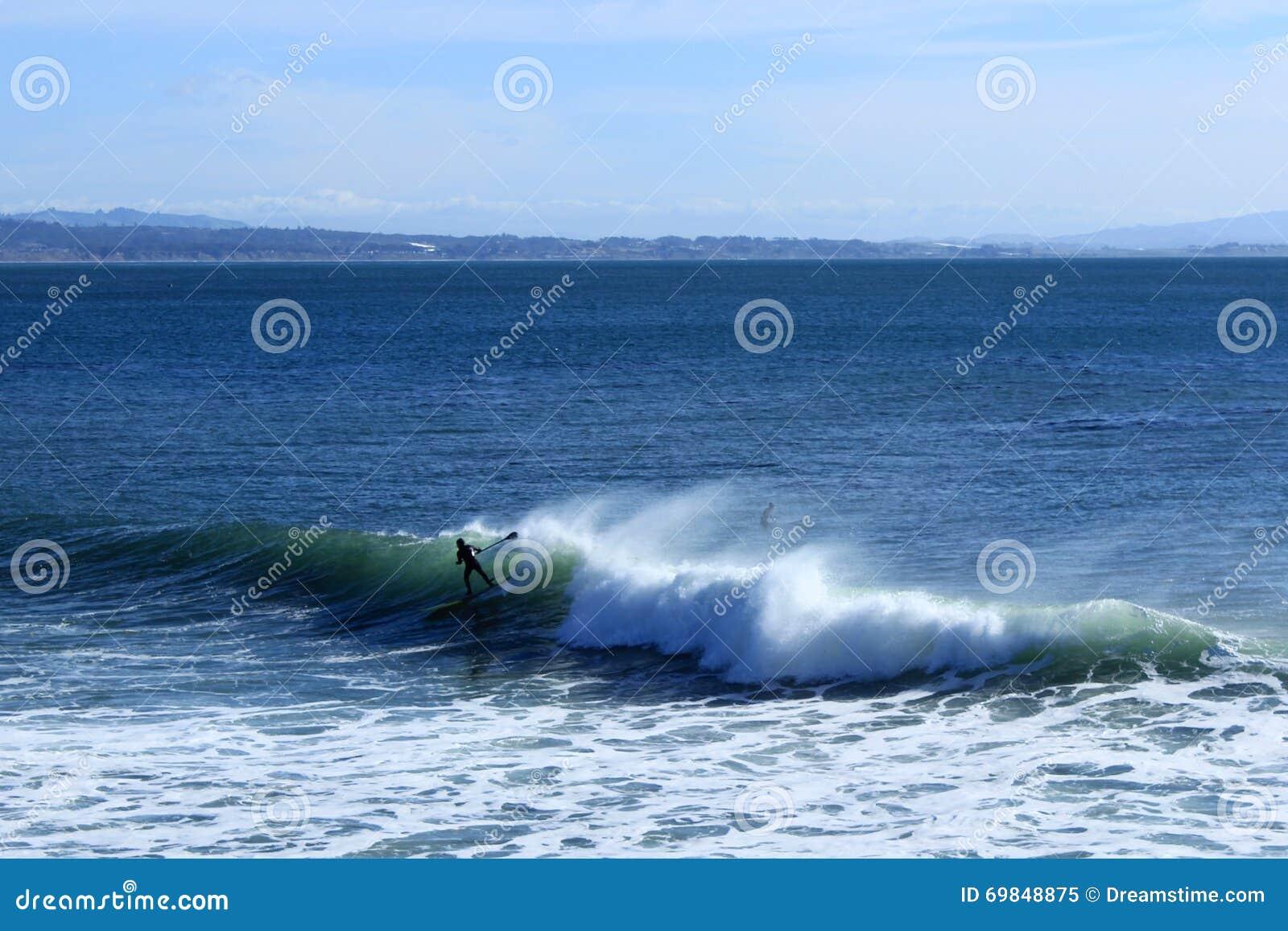 Paddleboarder едет волна в Santa Cruz