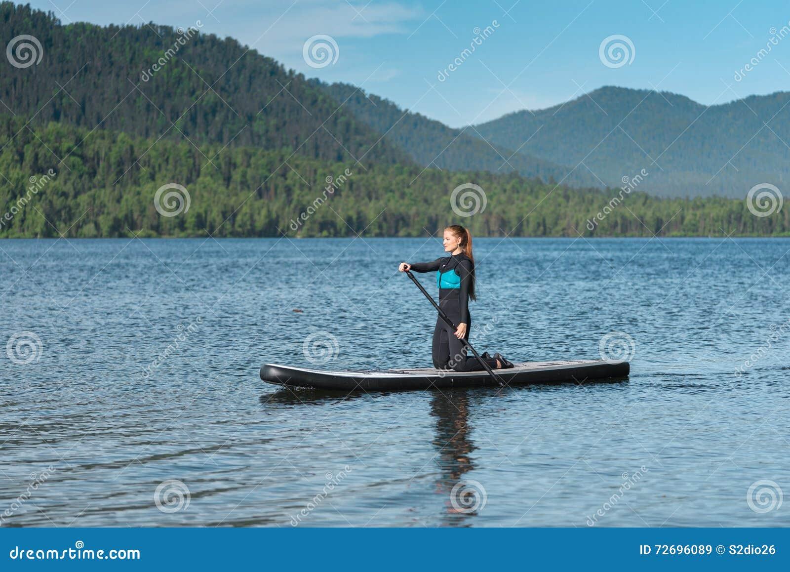 Paddleboarding在山湖的妇女