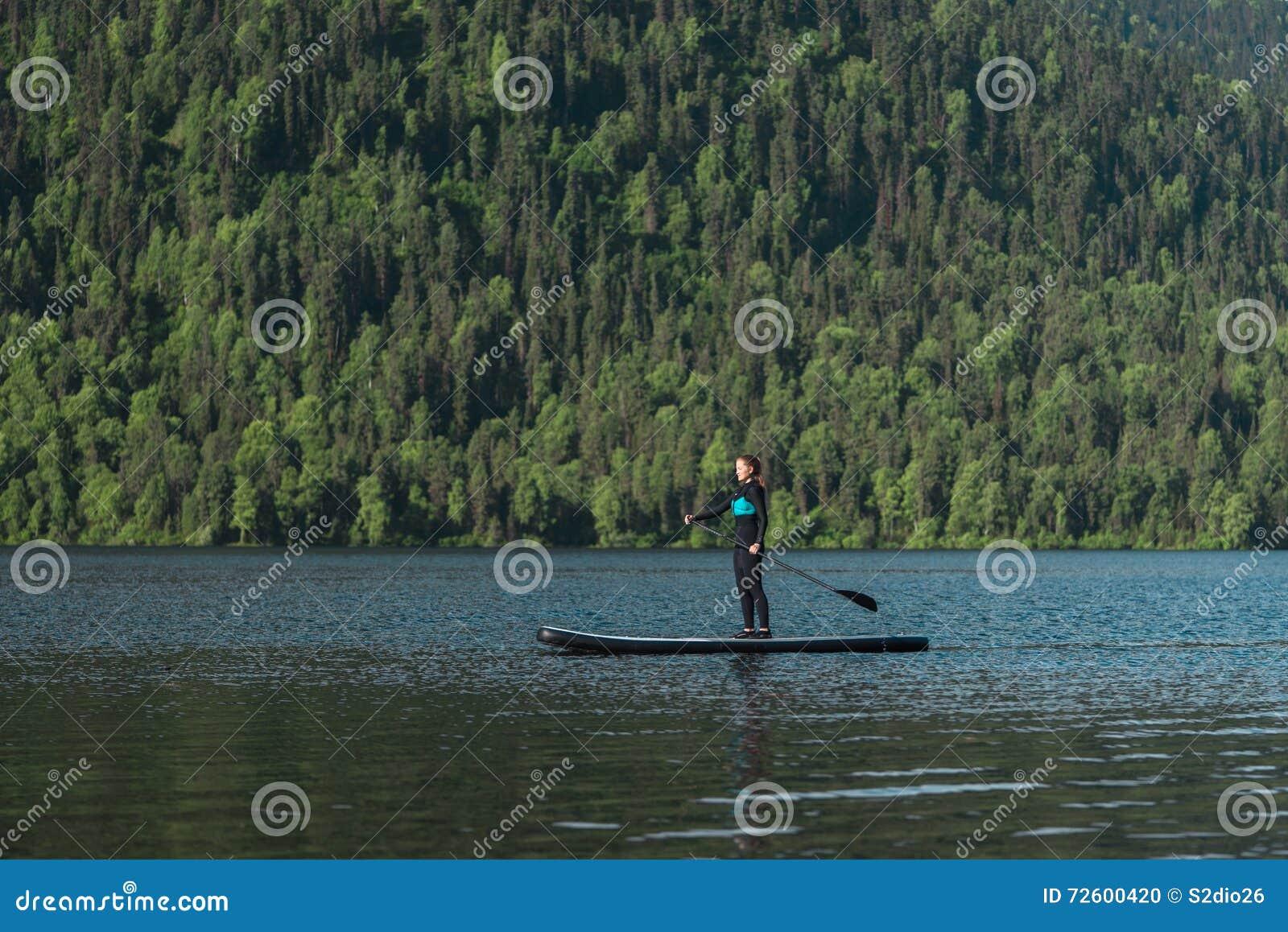 Paddleboarding在山湖的微笑的妇女