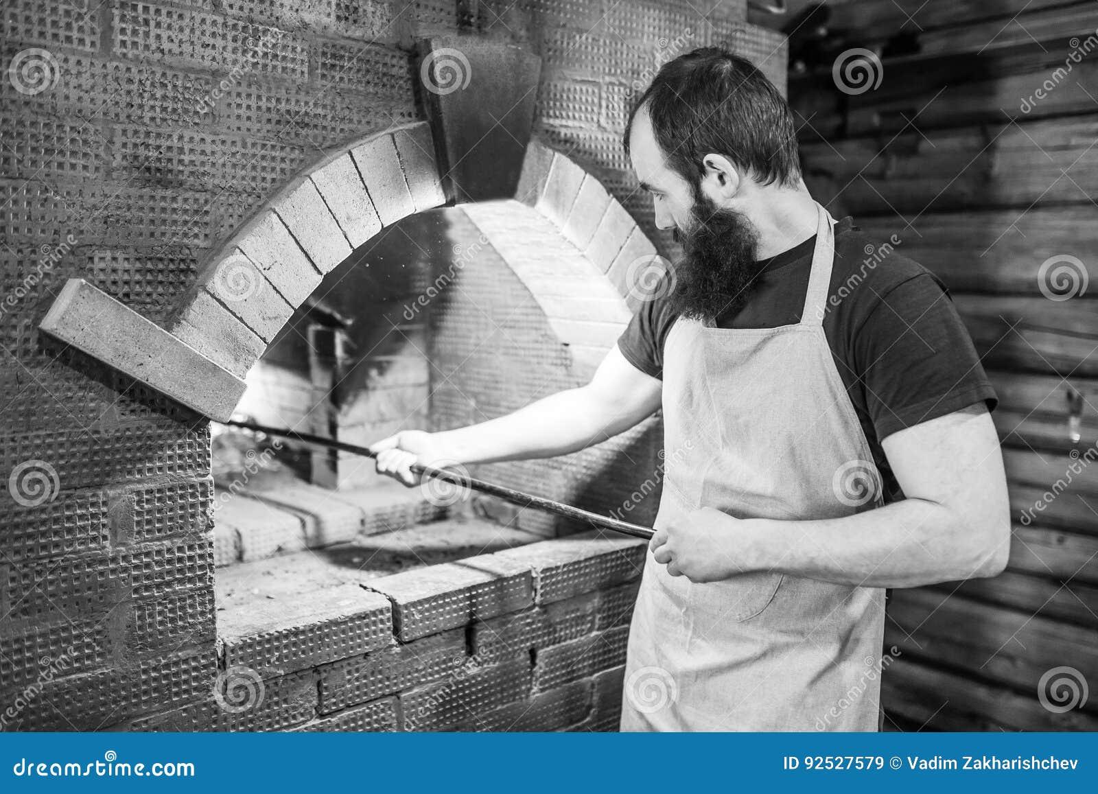 Padeiro masculino que cozinha o forno para cozinhar e agitado os carvões com o pôquer
