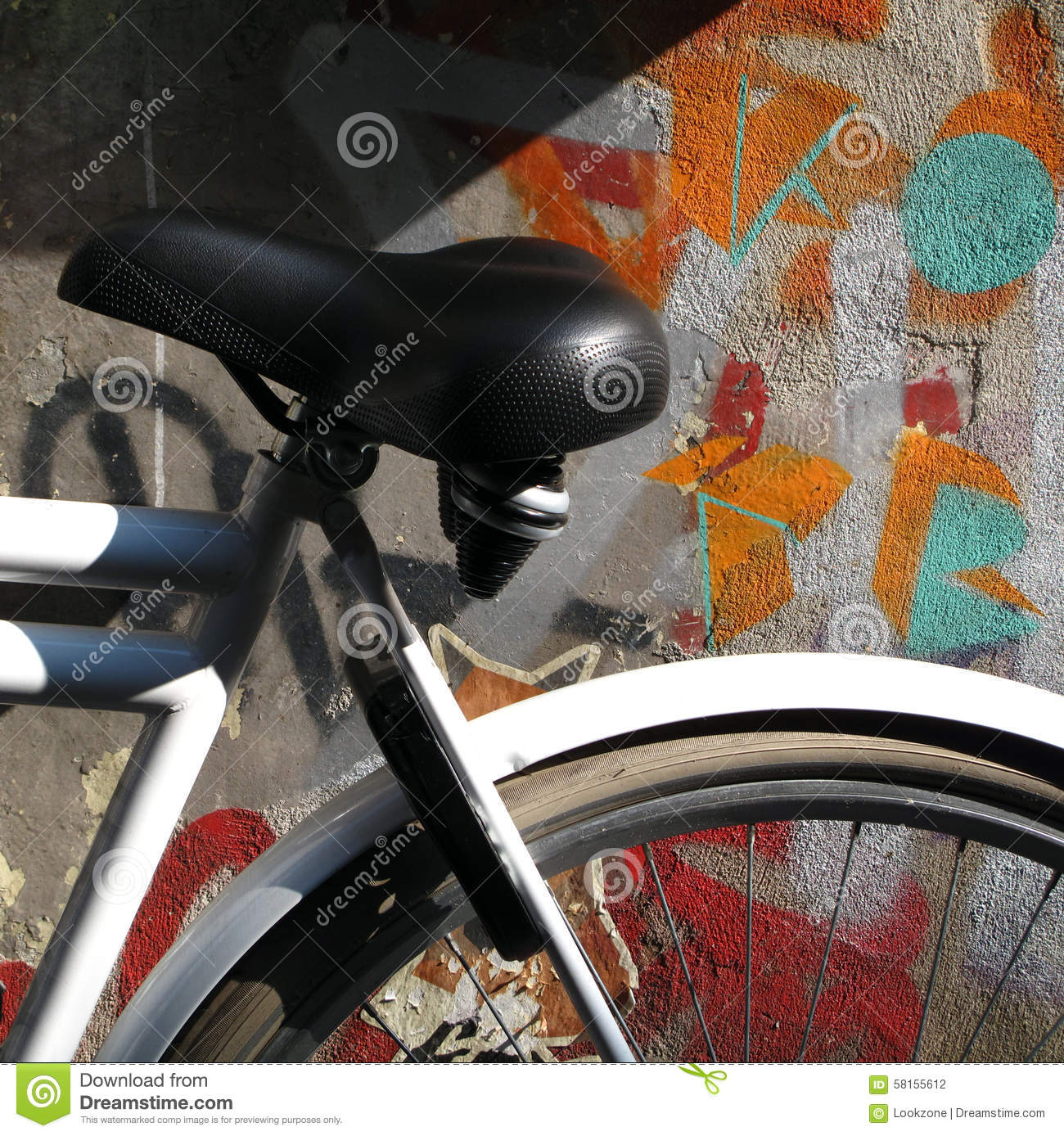 A white framed bicycle highlights the rich colors on a graffiti painted urban wall photo taken in amsterdam netherlands