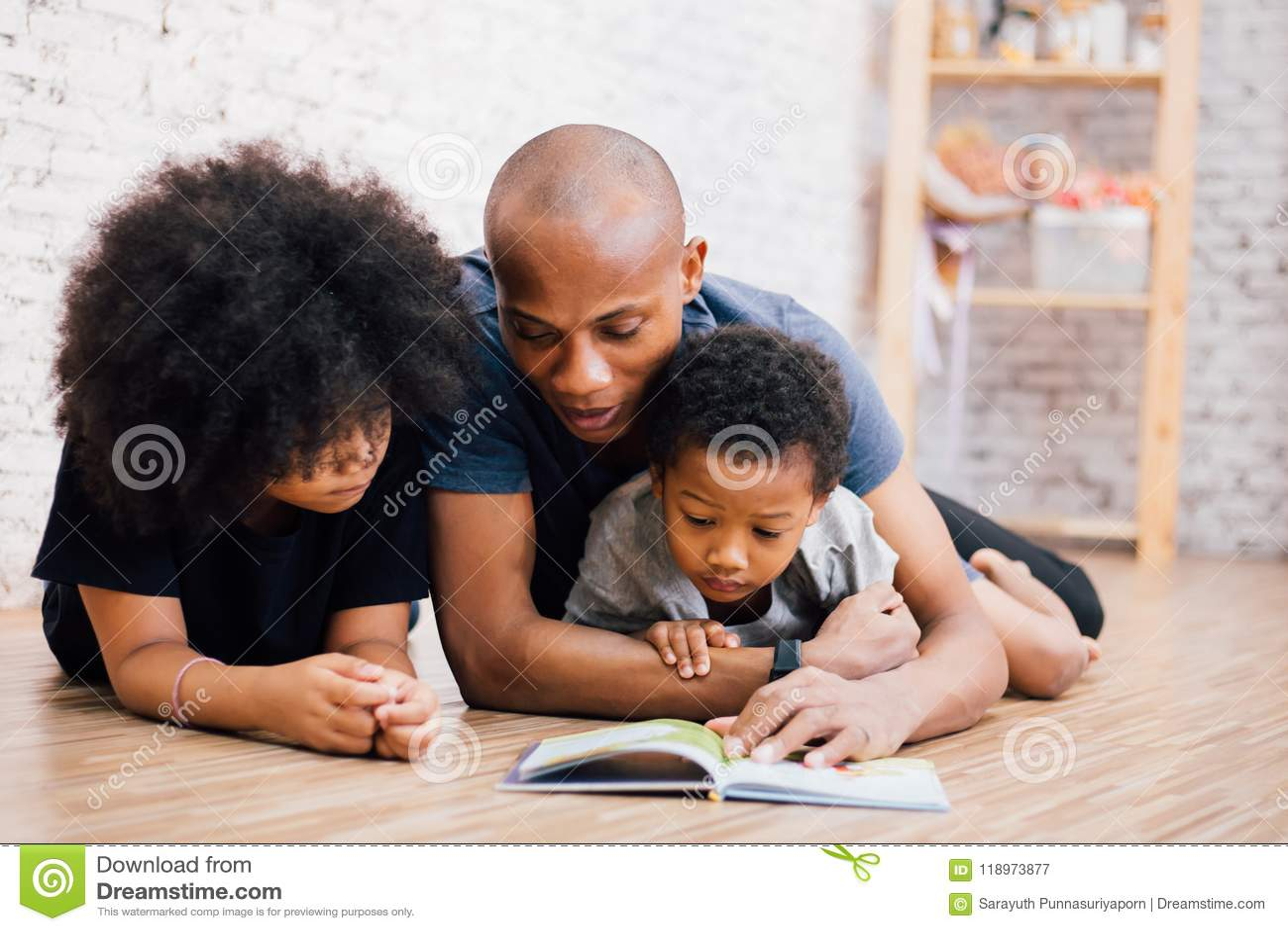 Padre afroamericano que lee una historia de la fábula del cuento de hadas para los niños en casa