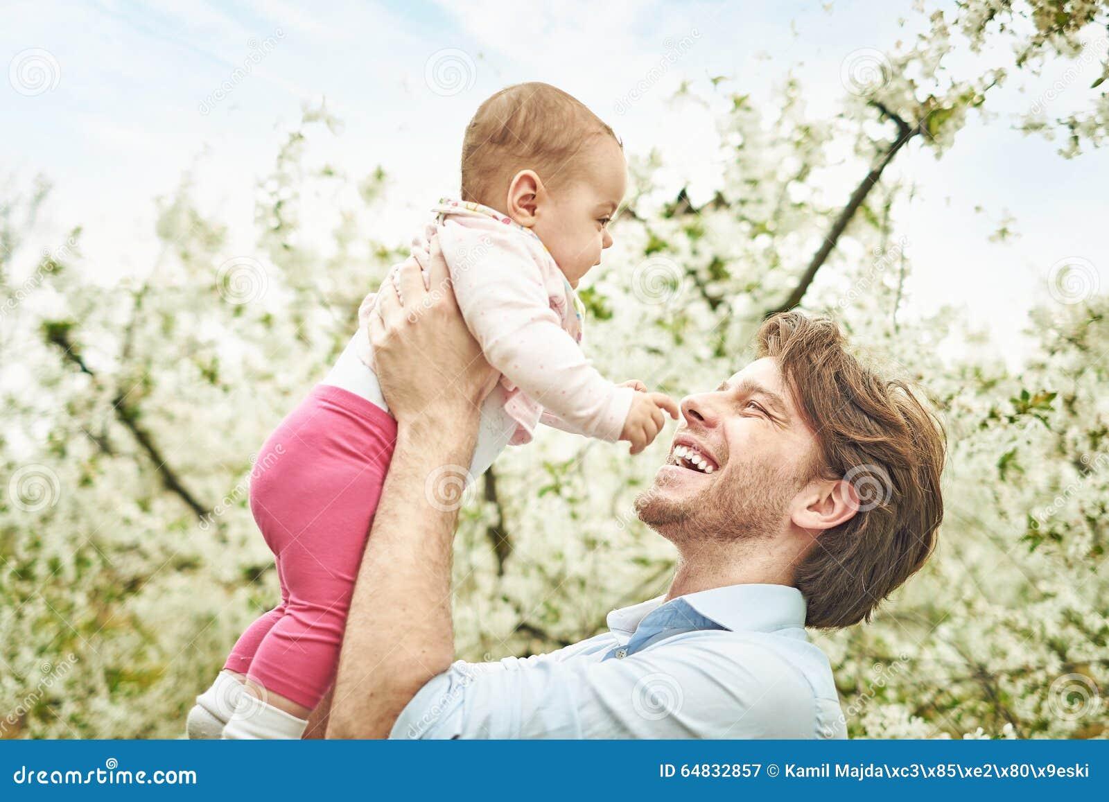 Padre alegre que sostiene el suyo que lleva a su niño querido