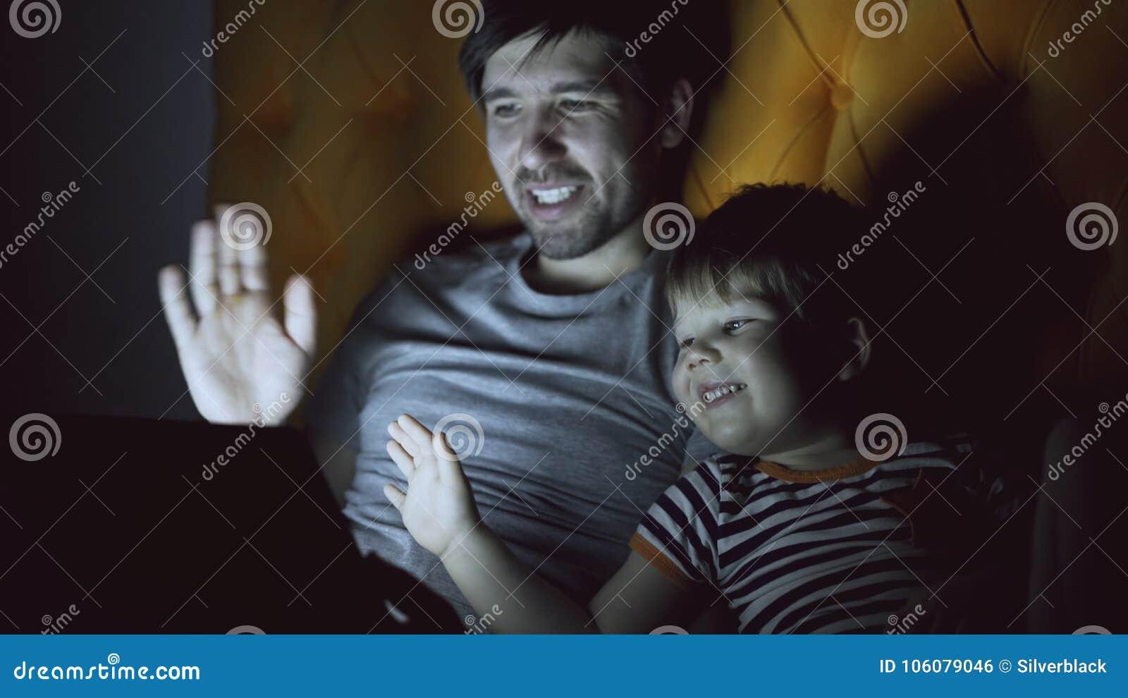 Padre amoroso e suo piccolo il figlio che hanno video chiacchierata online con i nonni che per mezzo del computer della compressa