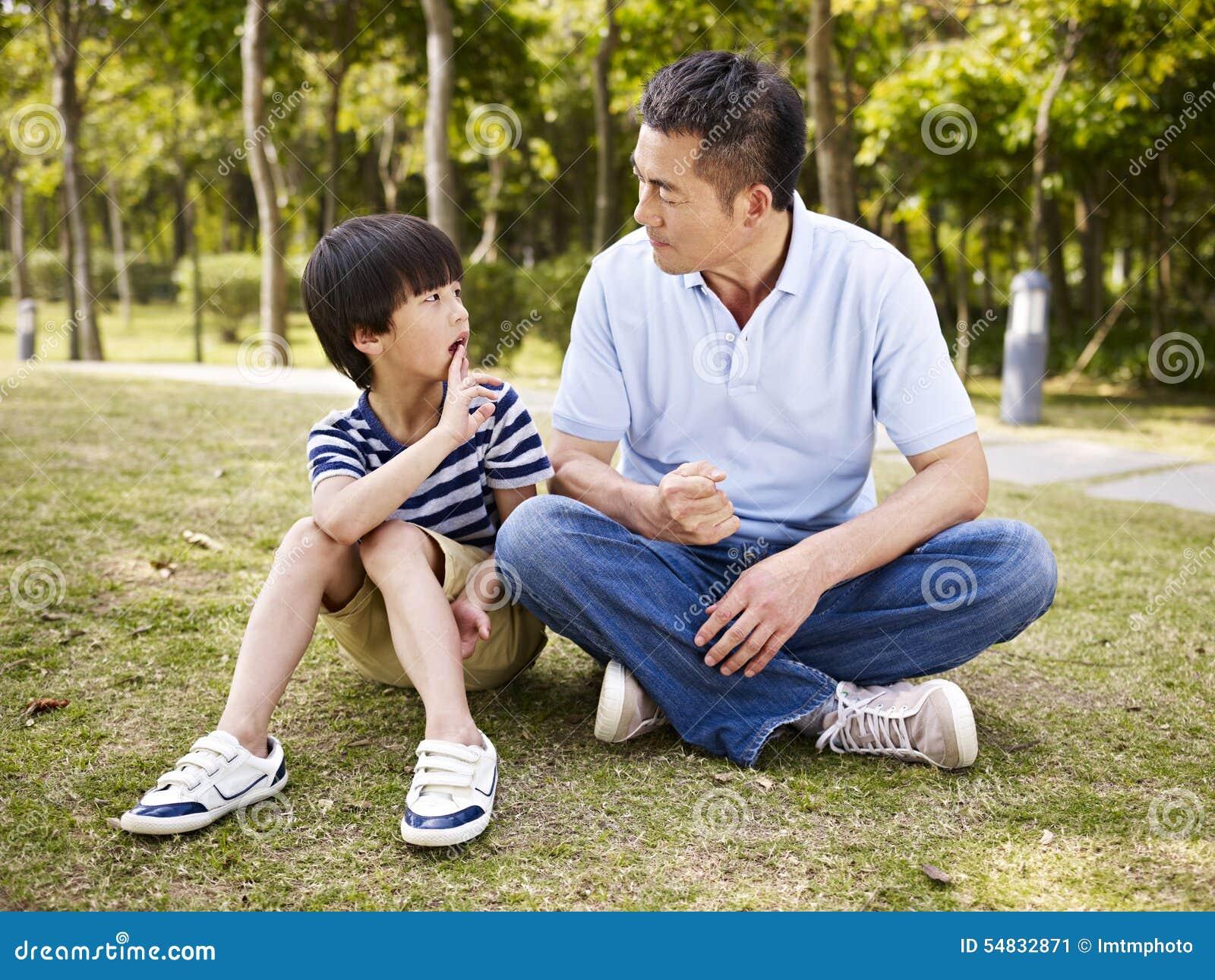Padre asiático e hijo que tienen una conversación