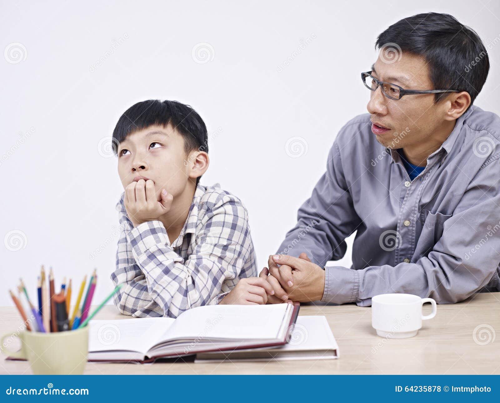 Padre asiático e hijo que tienen una conversación seria