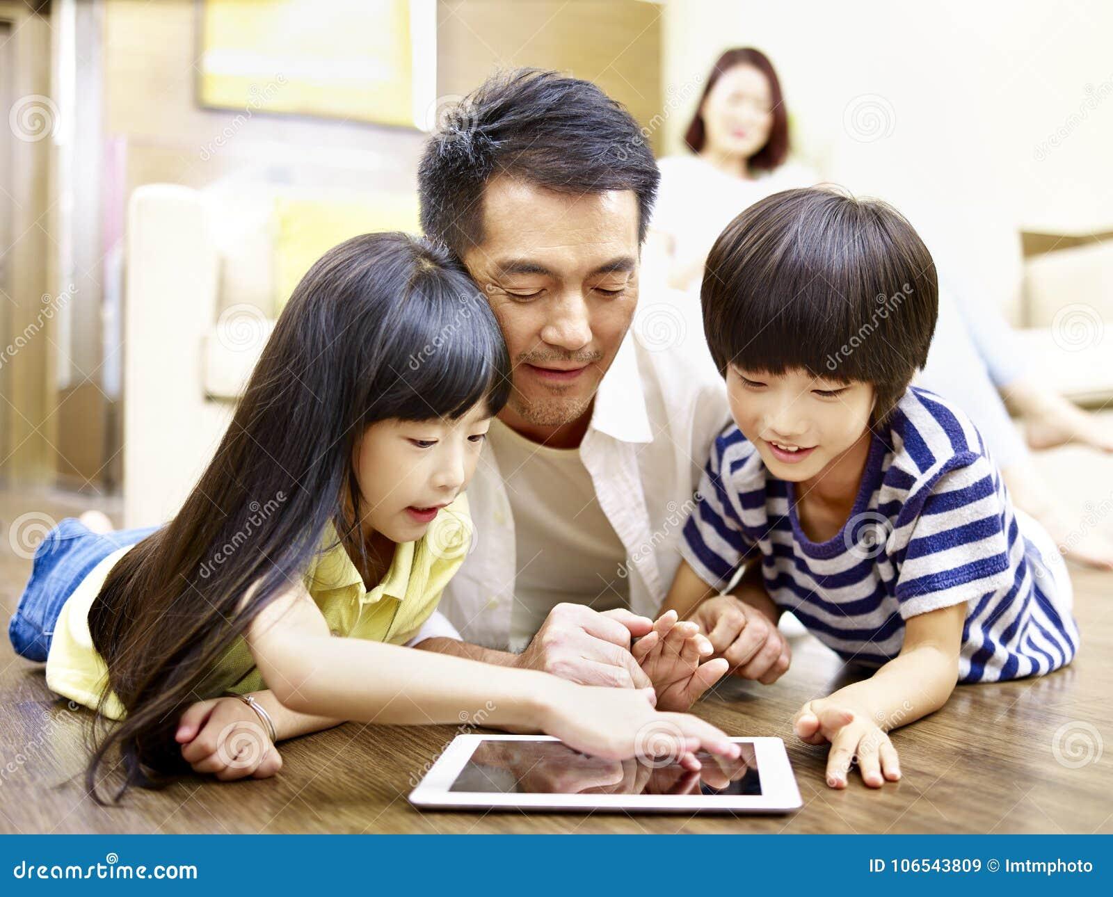 Padre asiático y dos niños que usan la tableta digital junto