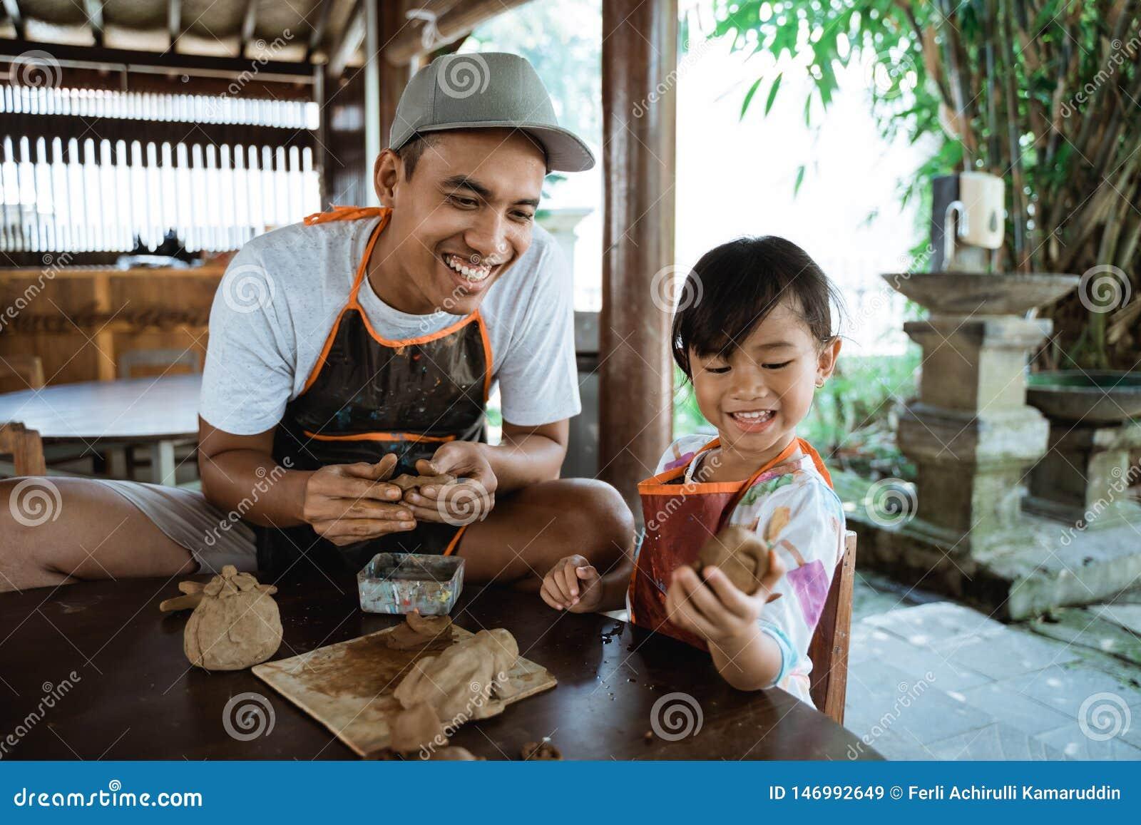 Padre asiatico e figlia che lavorano con l argilla