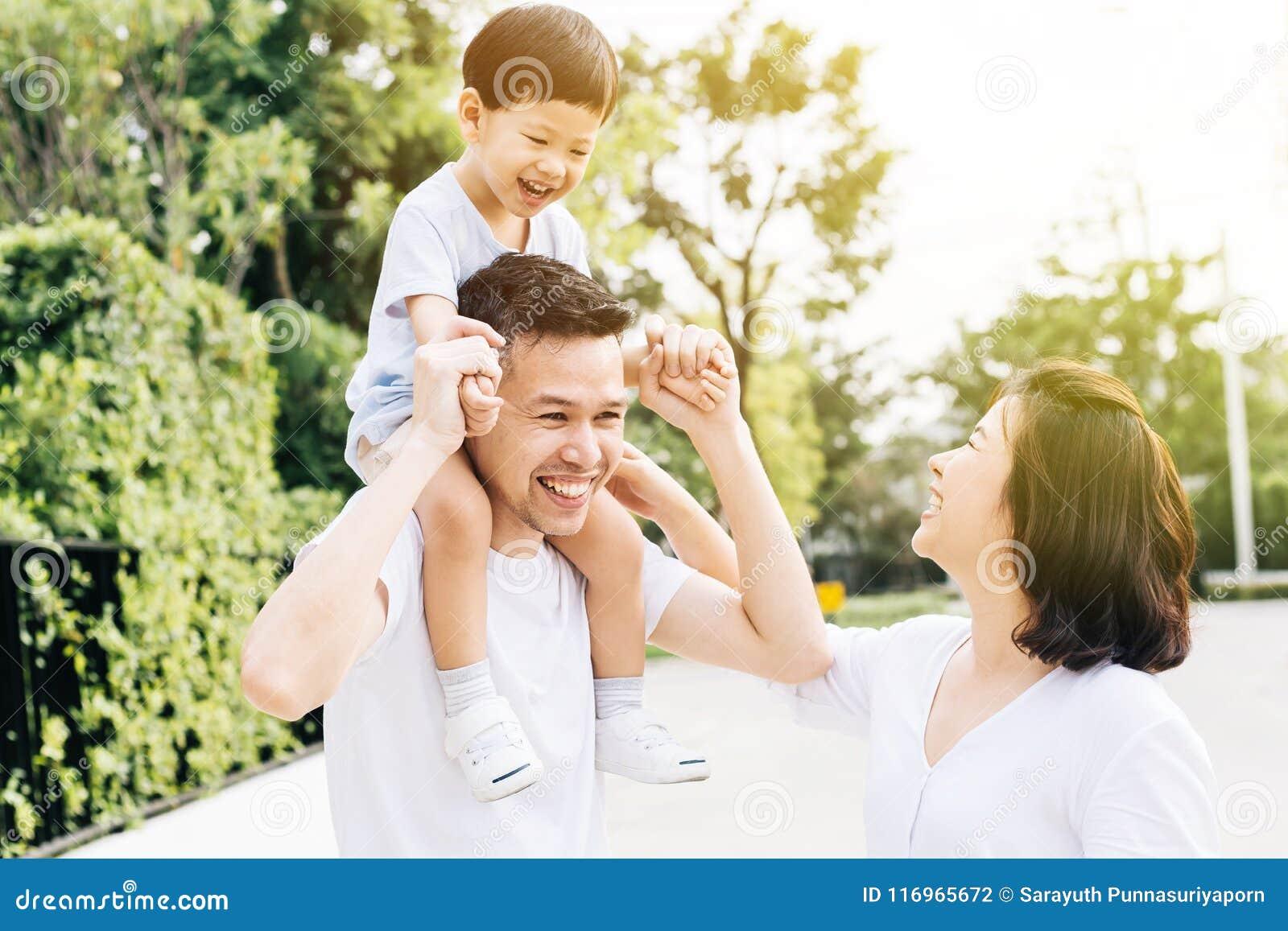 Padre asiatico sveglio che trasporta sulle spalle suo figlio con la sua moglie nel parco Famiglia emozionante che spende tempo in