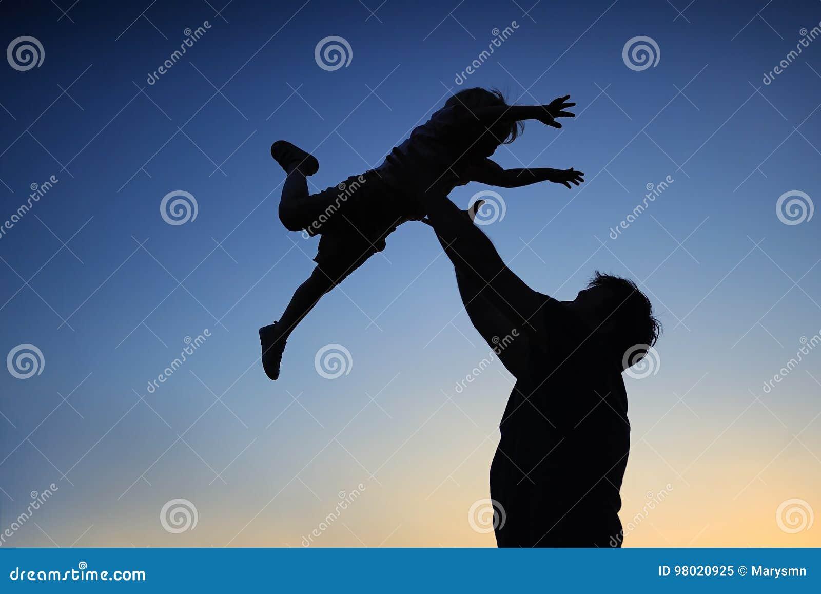 Padre cariñoso y su pequeño hijo que tienen fan junto al aire libre Familia como silueta en puesta del sol