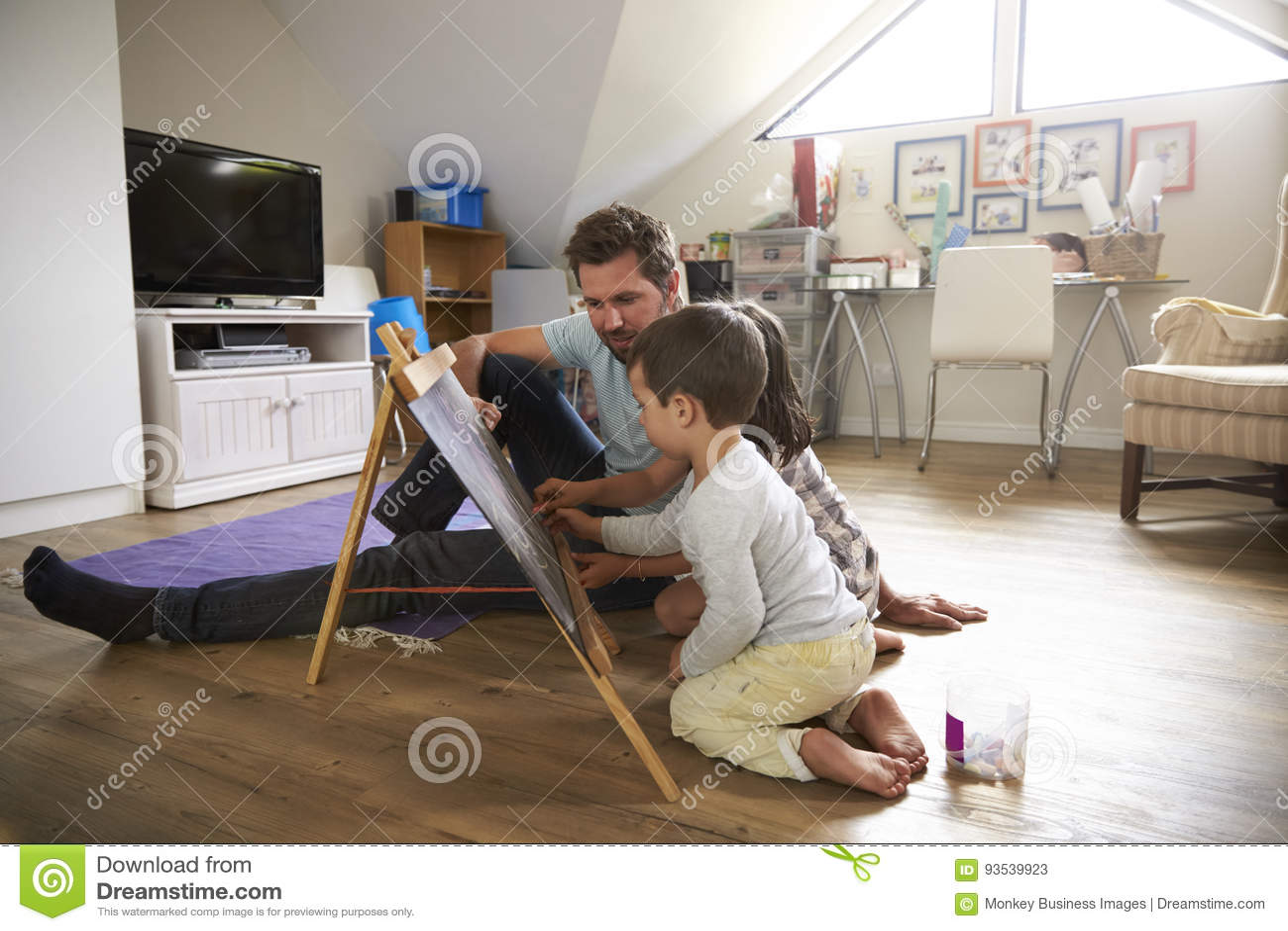 Padre And Children Drawing en la pizarra en sala de juegos
