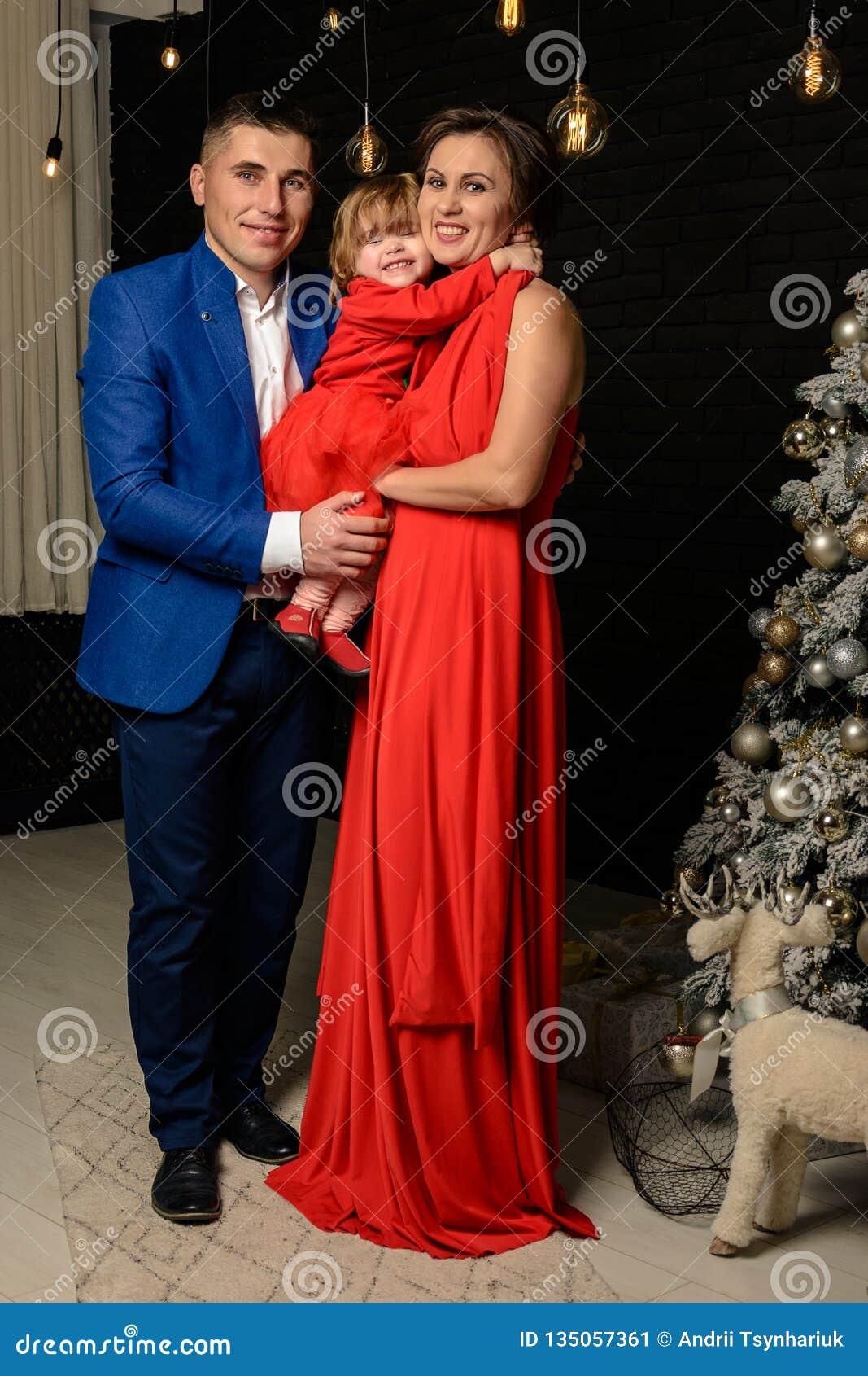 Padre con la madre e la loro condizione della figlia accanto ad una mamma dell albero di Natale con la figlia in vestiti rossi