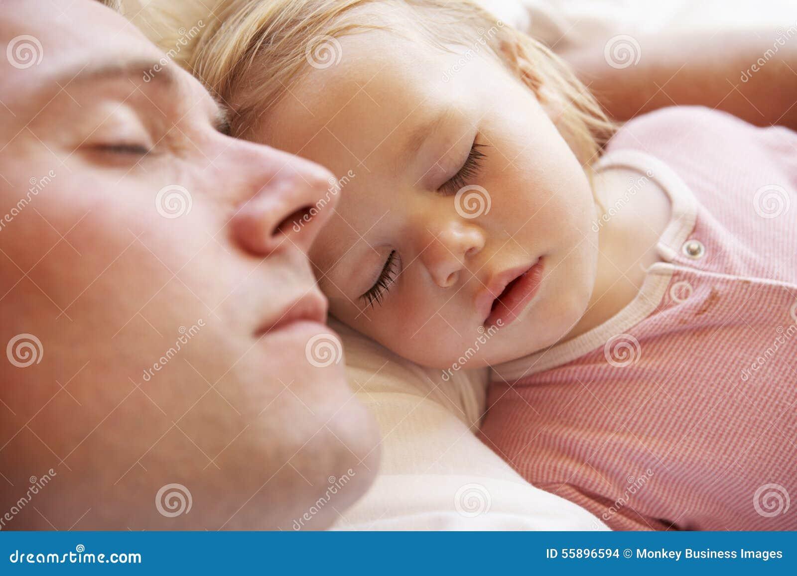 Padre And Daughter Sleeping en cama