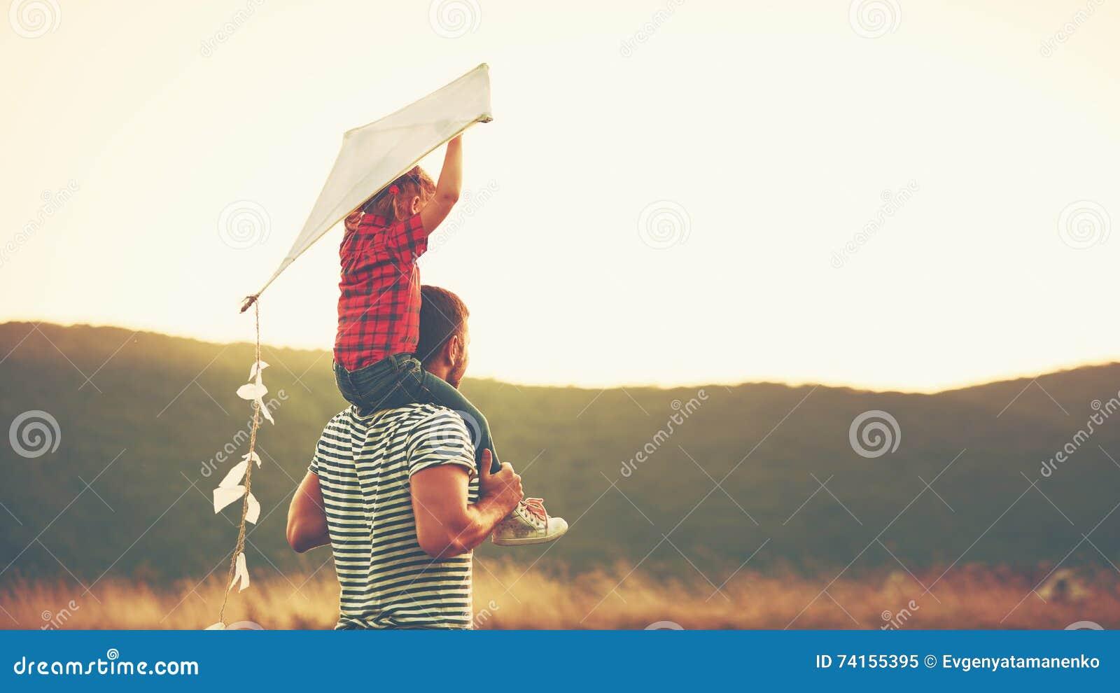 Padre e bambino felici della famiglia sul prato con un aquilone di estate
