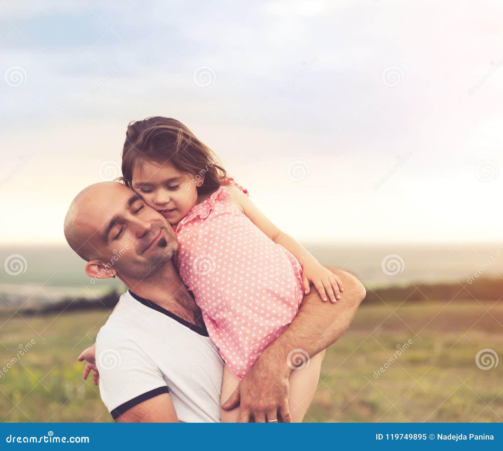 Padre e hija que abrazan en puesta del sol del verano