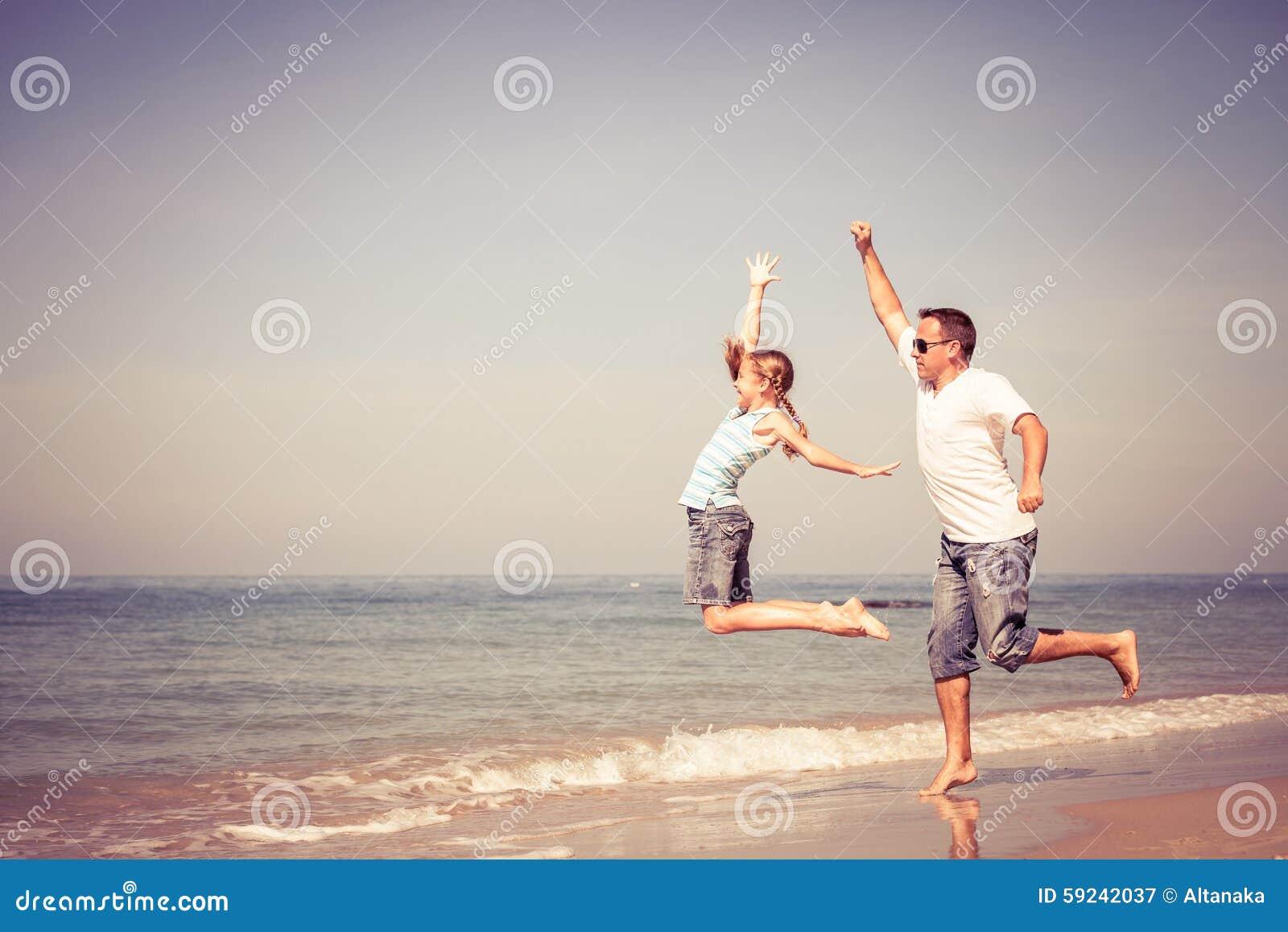 Padre e hija que juegan en la playa en el tiempo del día