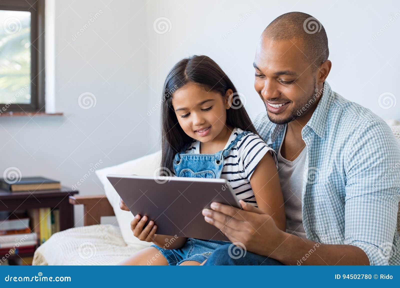 Padre e hija que usa la tableta