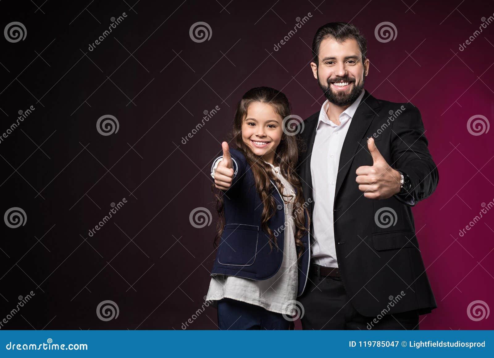 Padre e hija sonrientes que muestran los pulgares para arriba