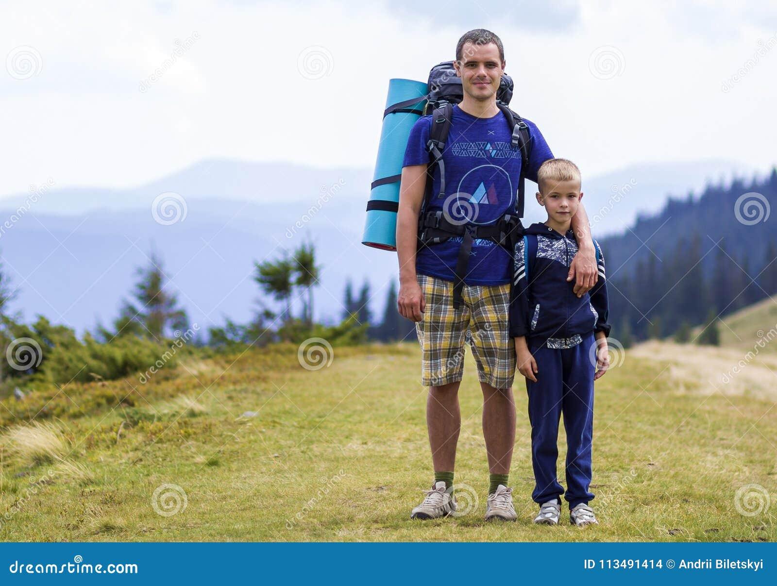 Padre e hijo con las mochilas que caminan junto en montañas escénicas del verde del verano Papá y niño que se colocan de goce de