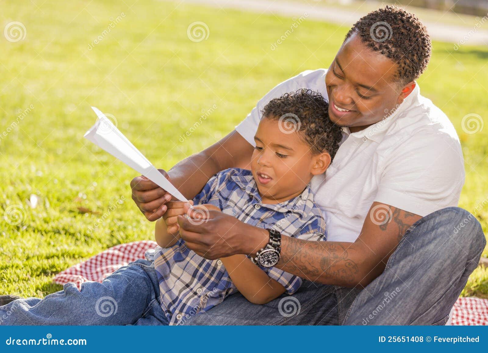 Padre e hijo de la raza mezclada que juegan los aeroplanos de papel