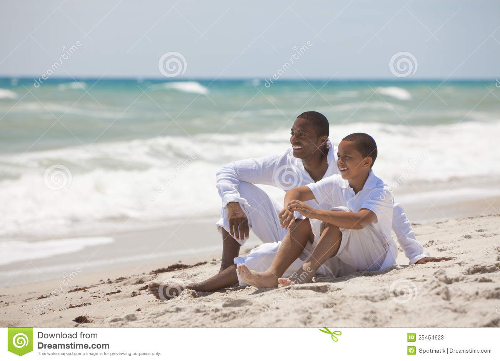 Padre e hijo felices del afroamericano en la playa